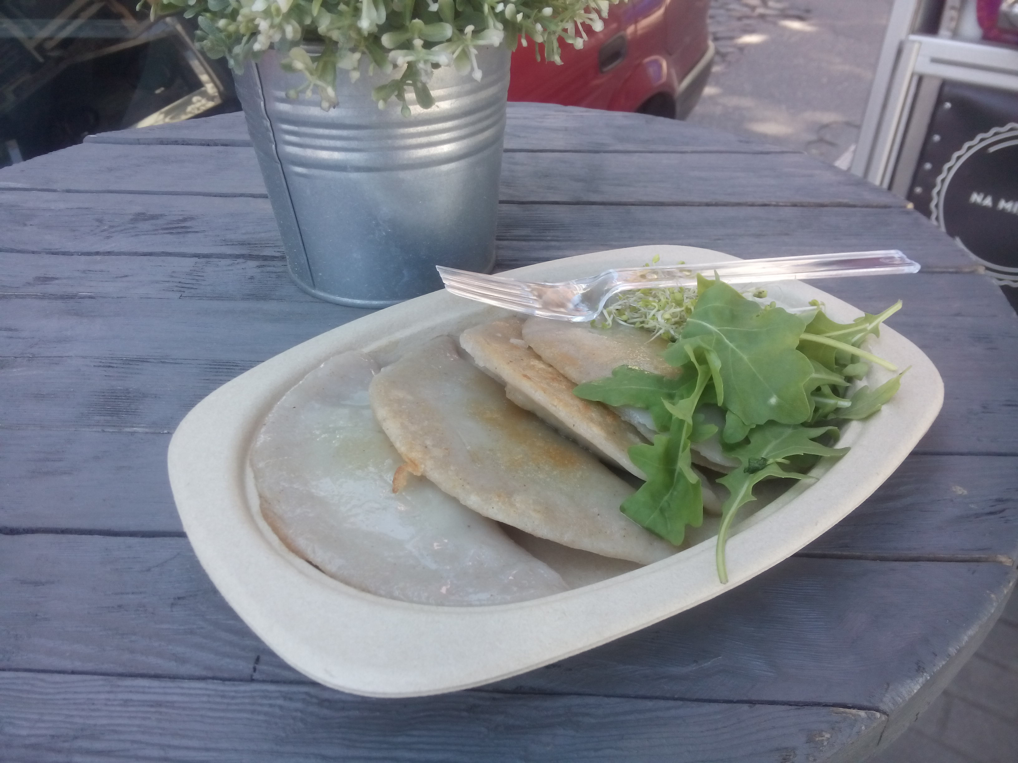 A wooden table with a metal plant pot and a cardboard plate containing four half-circle pierogi, plus salad