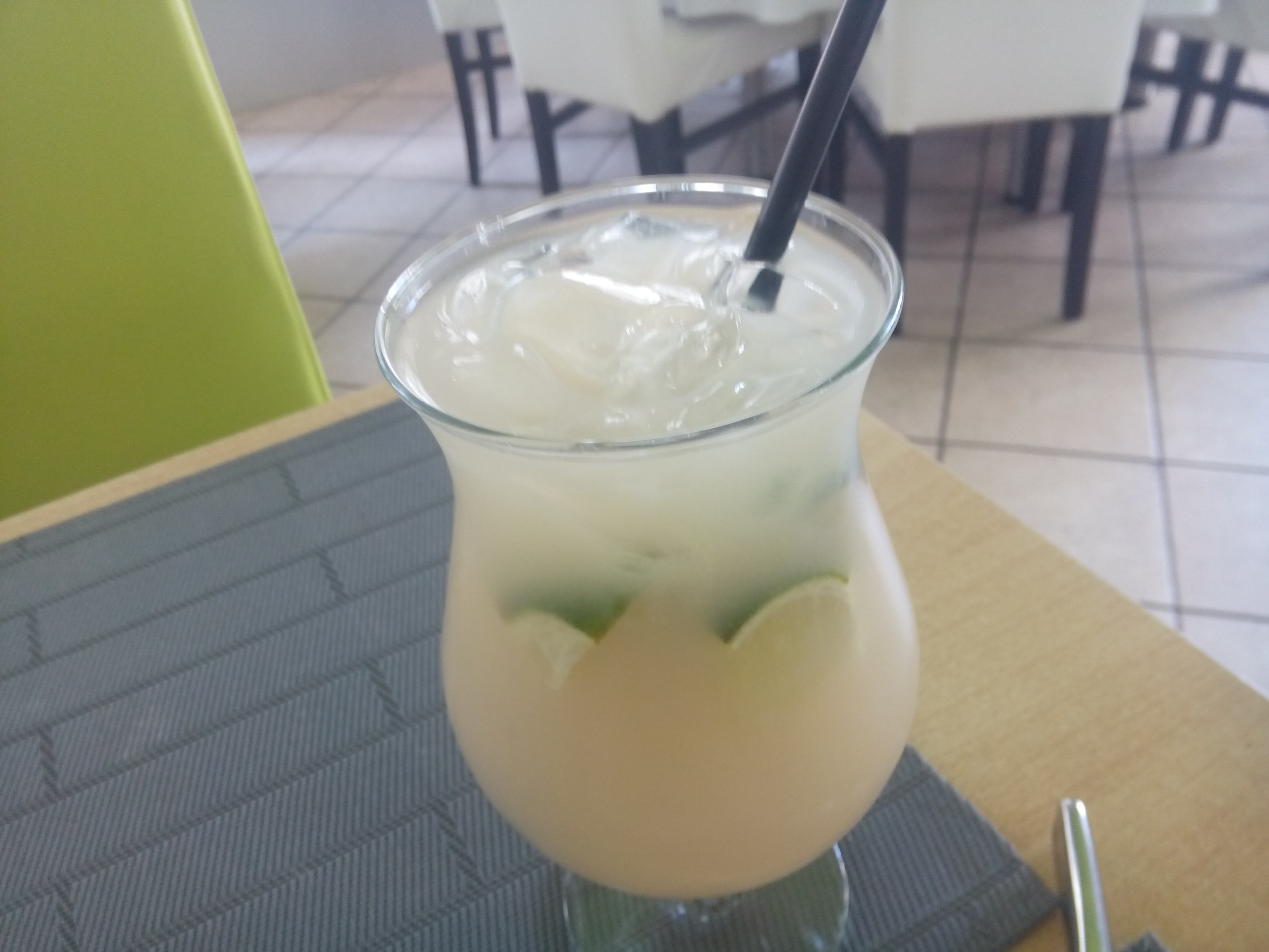 A large cocktail glass with a cloudy liquid and a straw