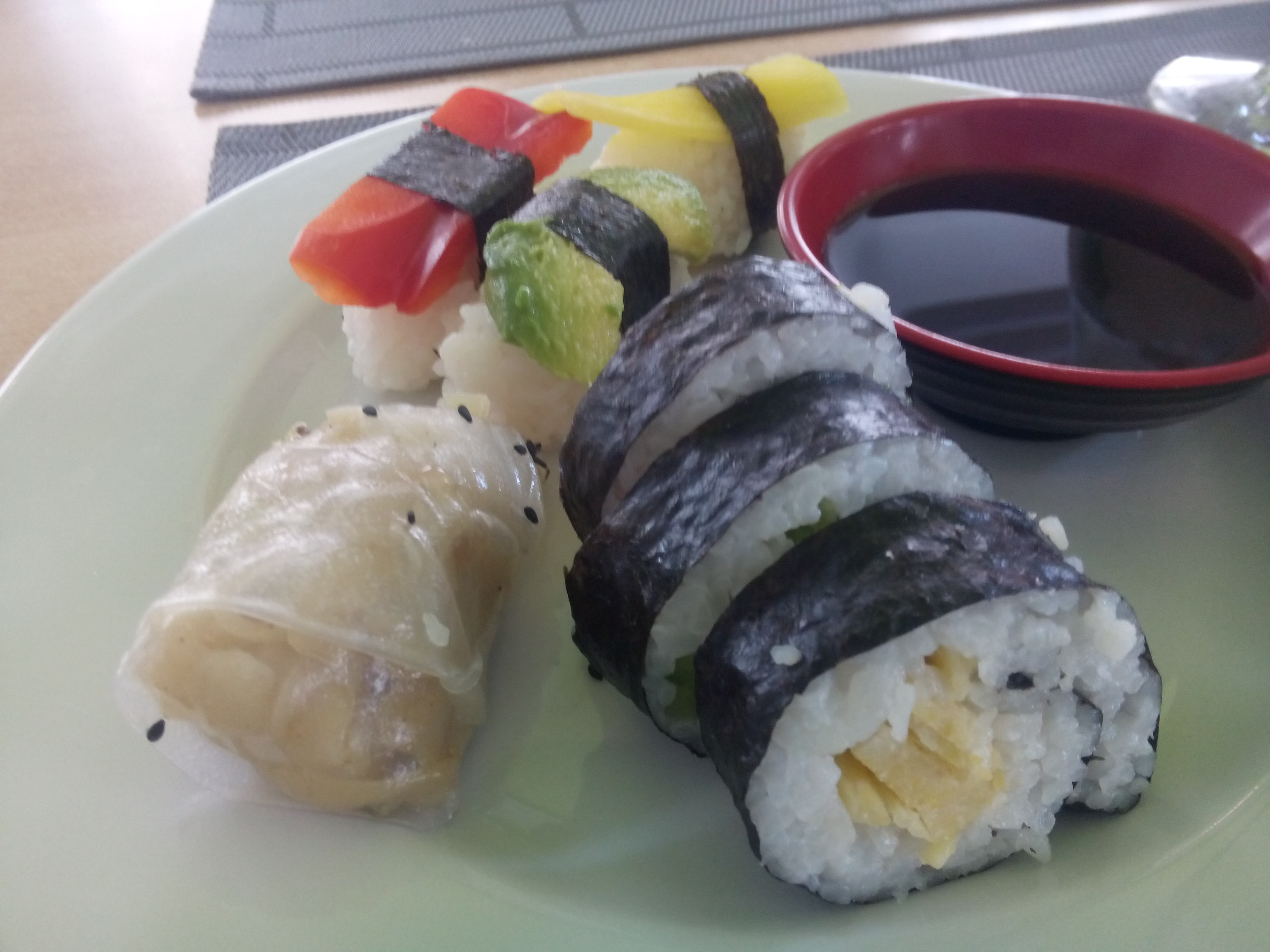A white plate with sushi rolls and summer rolls and a pot of soya sauce