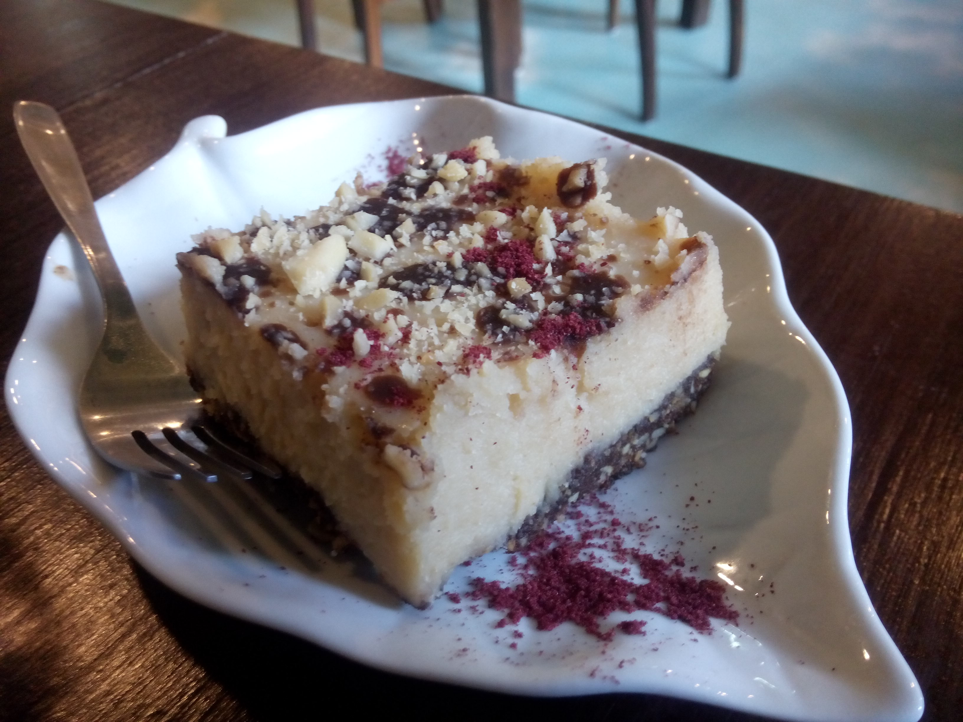 A leaf shaped white plate with a large chunk of cheesecake with chocolate and nuts and a fork