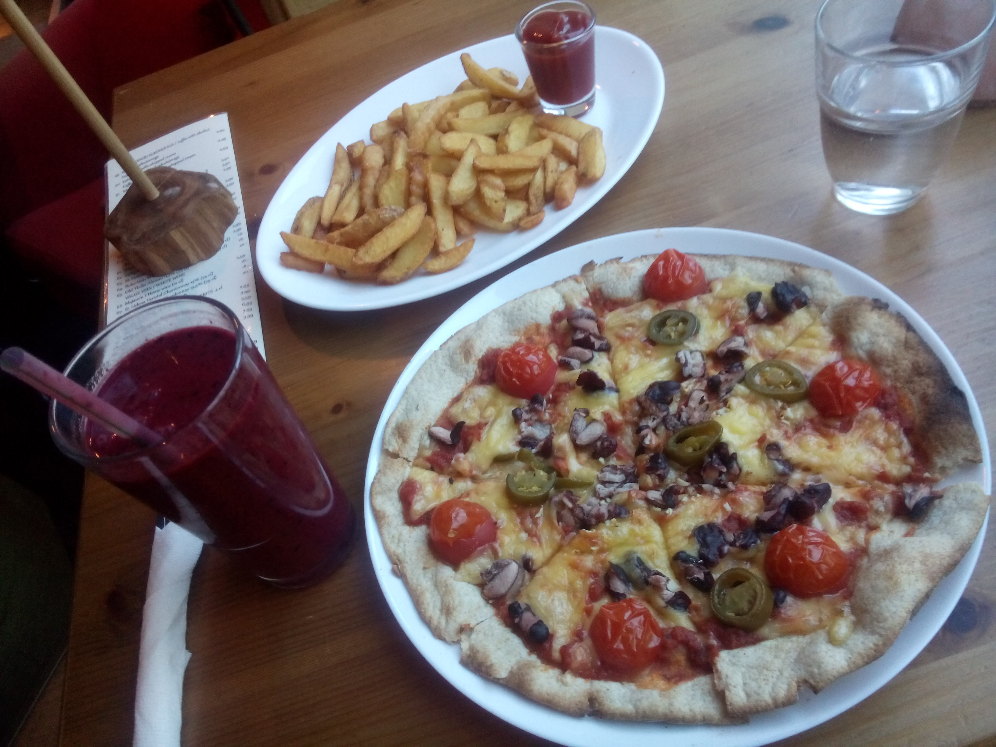 A wooden table with a purple smoothie in a glass, and two plates with fries and a pizza