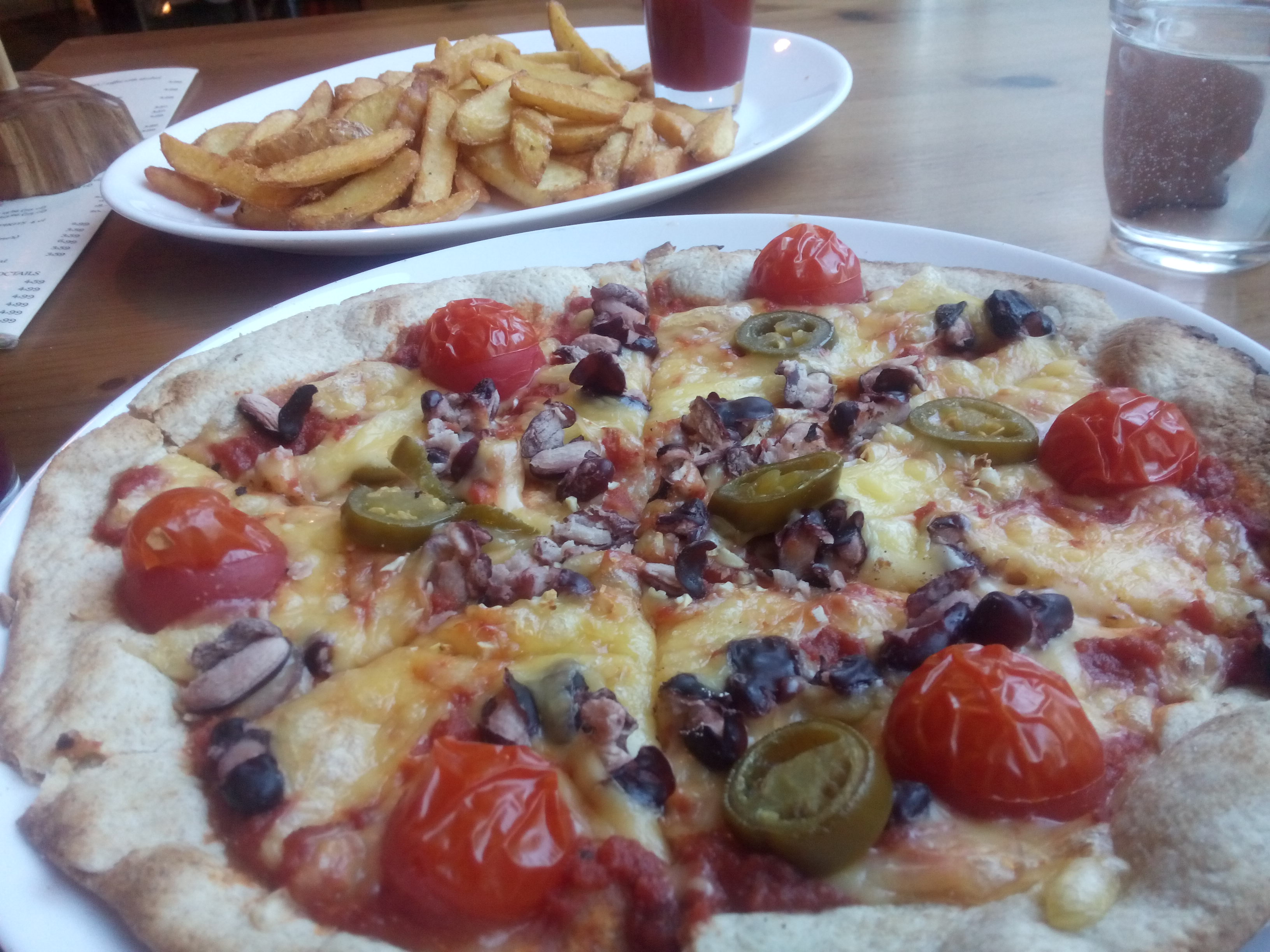 A close up of a pizza in the foreground with beans, jalapenos and tomatoes, and a plate of fries in the background