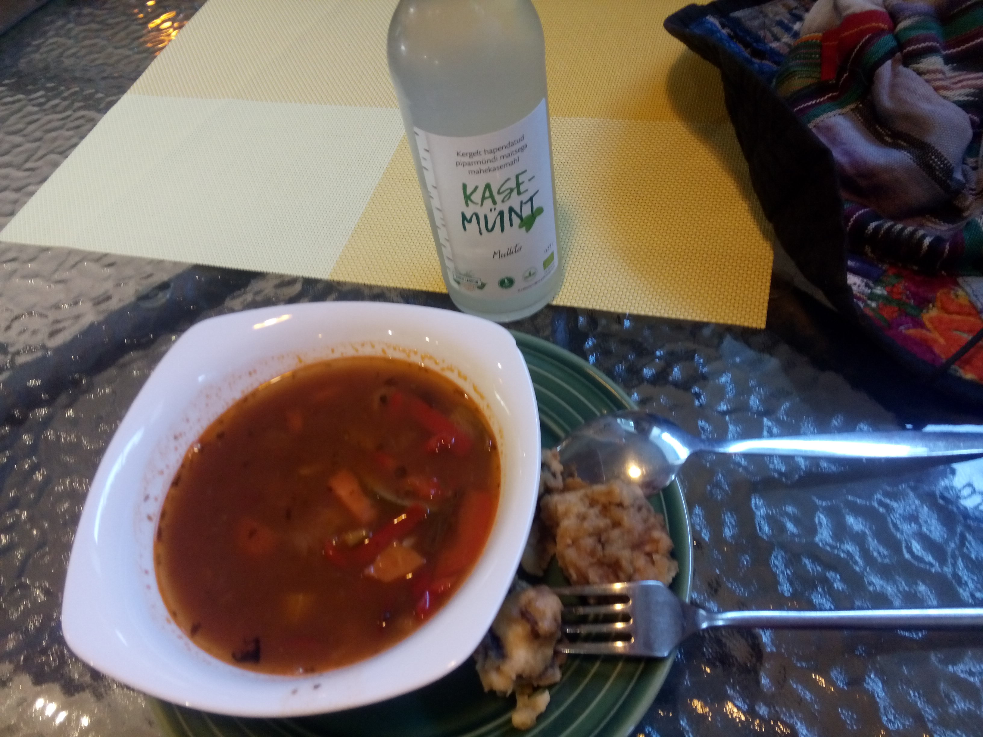 A glass table with a bowl of red soup on a plate and something fried on the side