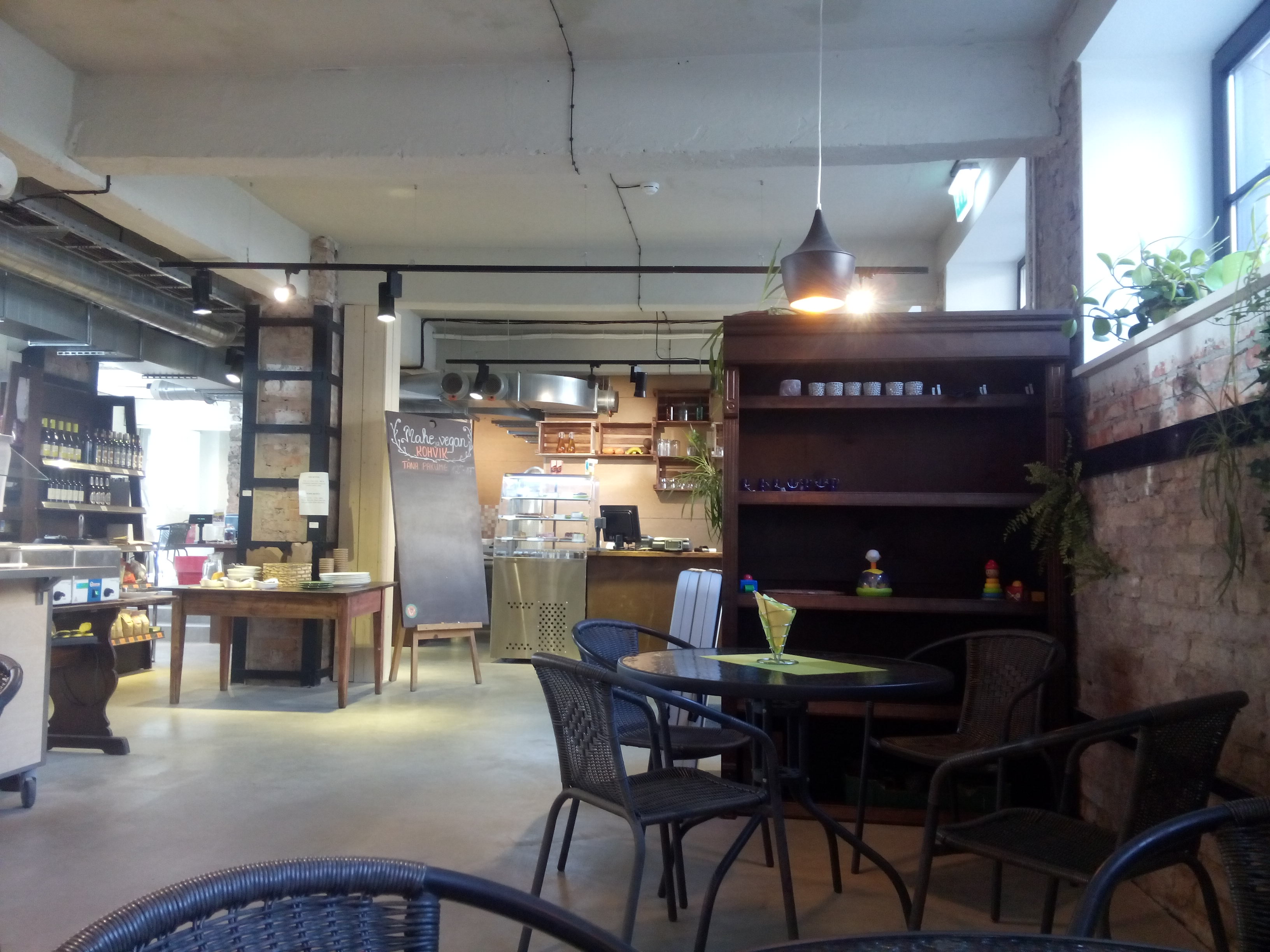A cafe and shop interior with metal chairs and tables, wooden shelves and a counter in the distance