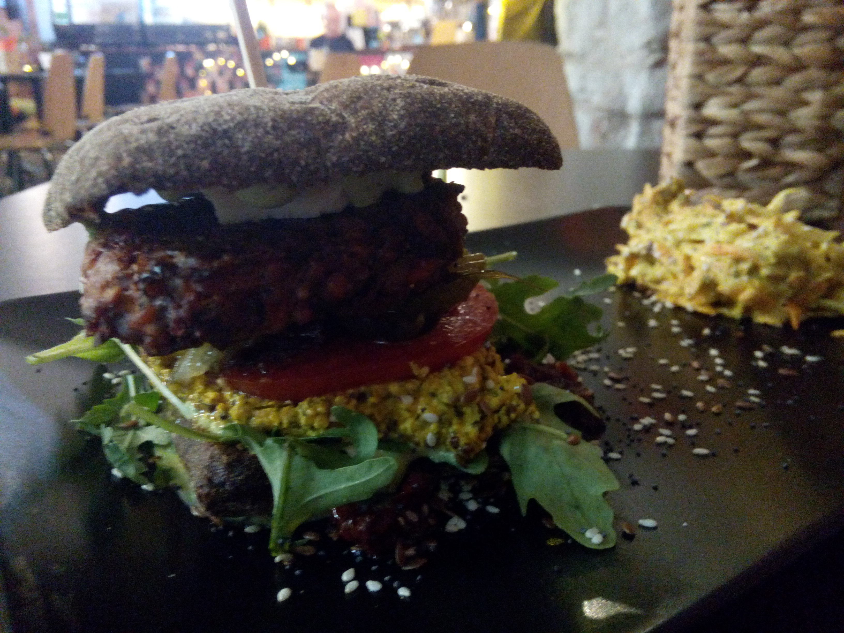 Side view of a towering burger on a black tray, with a fat patty and bright coloured salad
