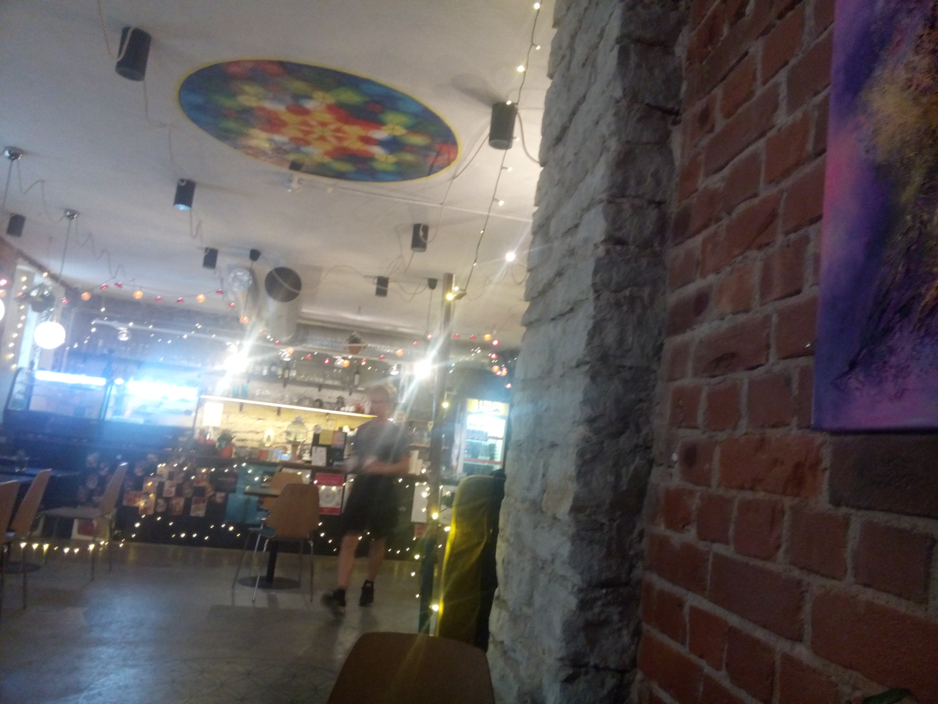 A brick wall to the right leads to the interior of a cafe with lots of lights and bright colours