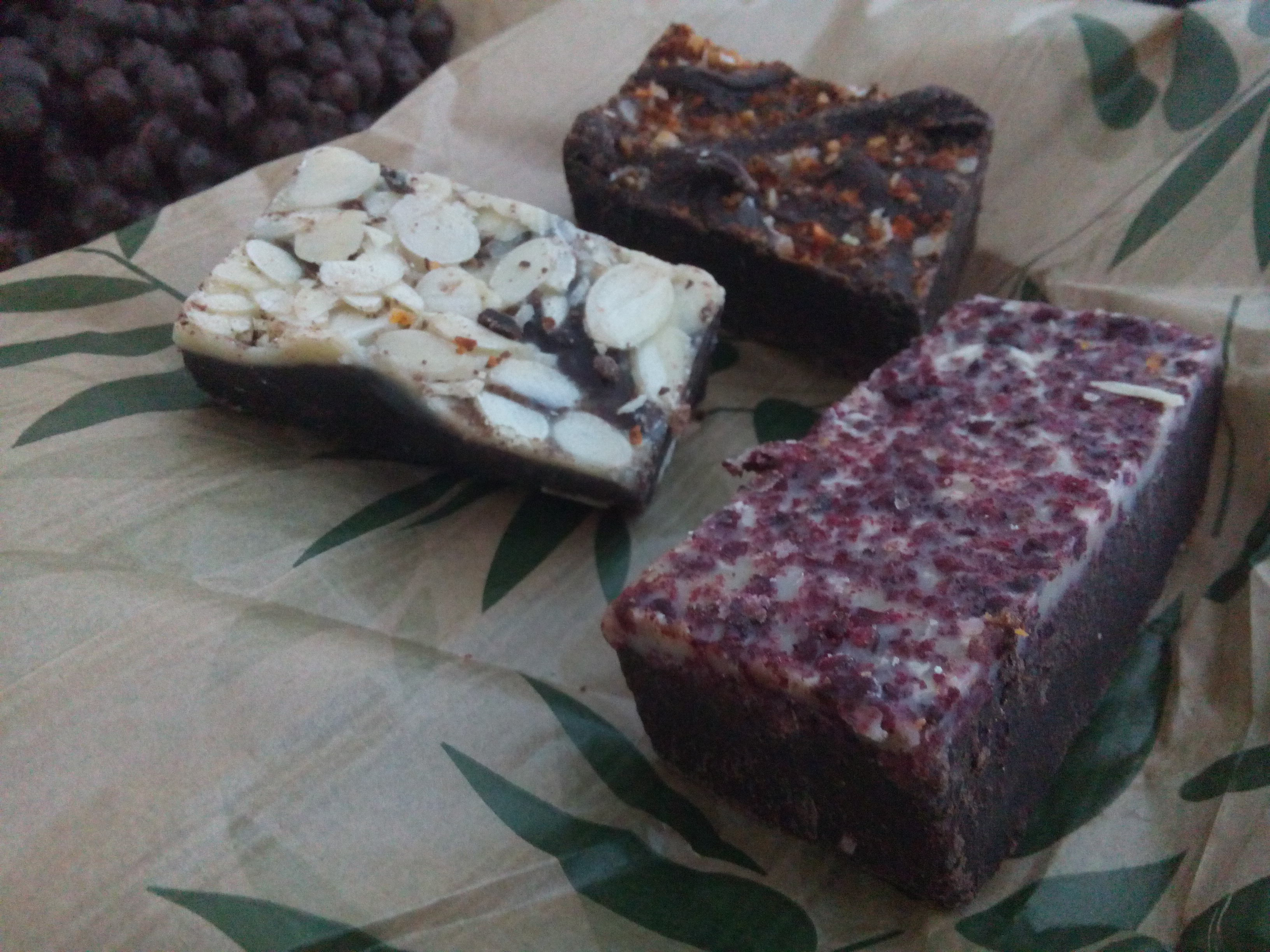 Three slabs of chocolate with different coloured toppings on a brown paper bag