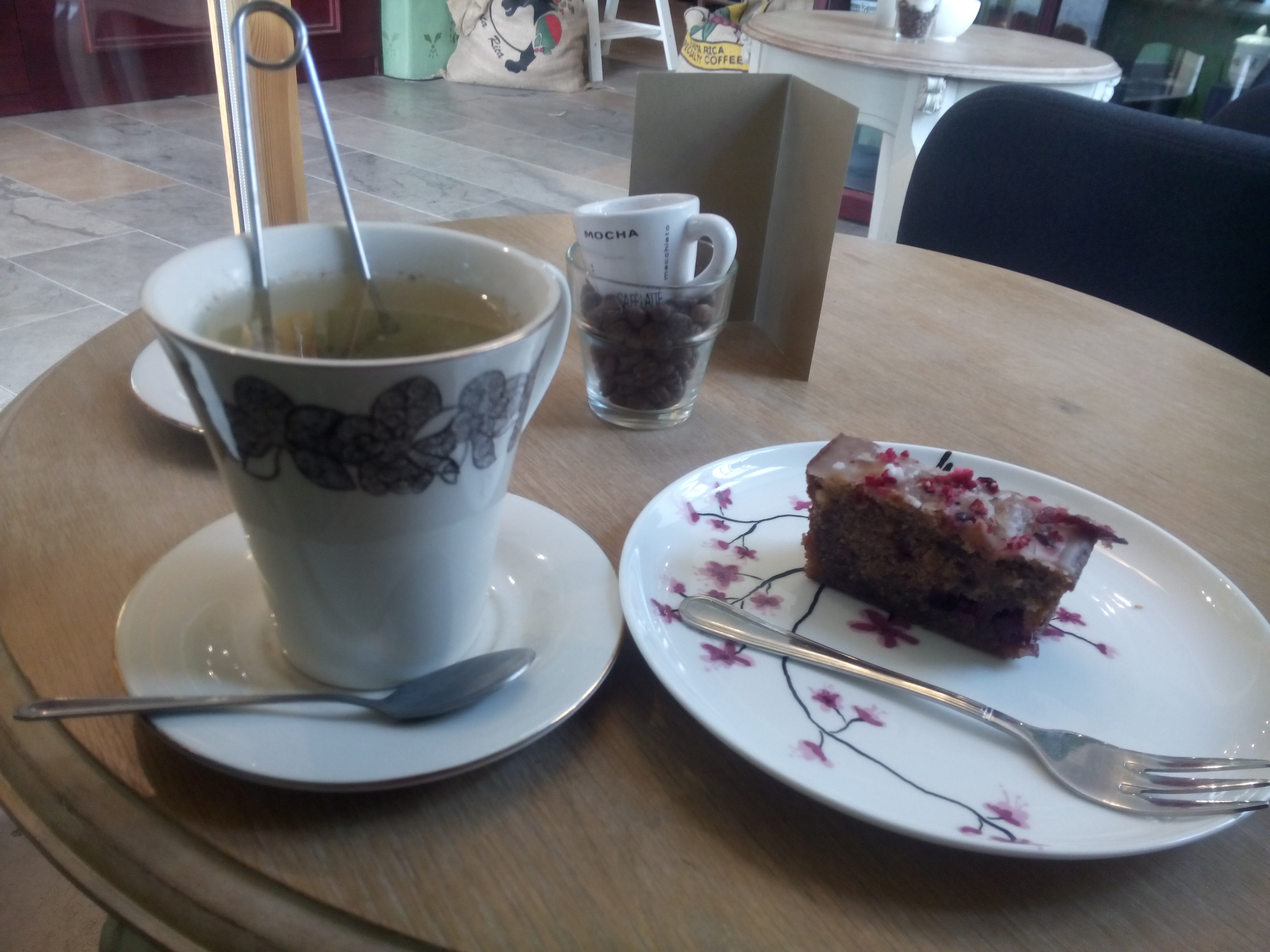 Two china plates on a table, one with a cup of green tea, the other with a slice of iced cake and a fork
