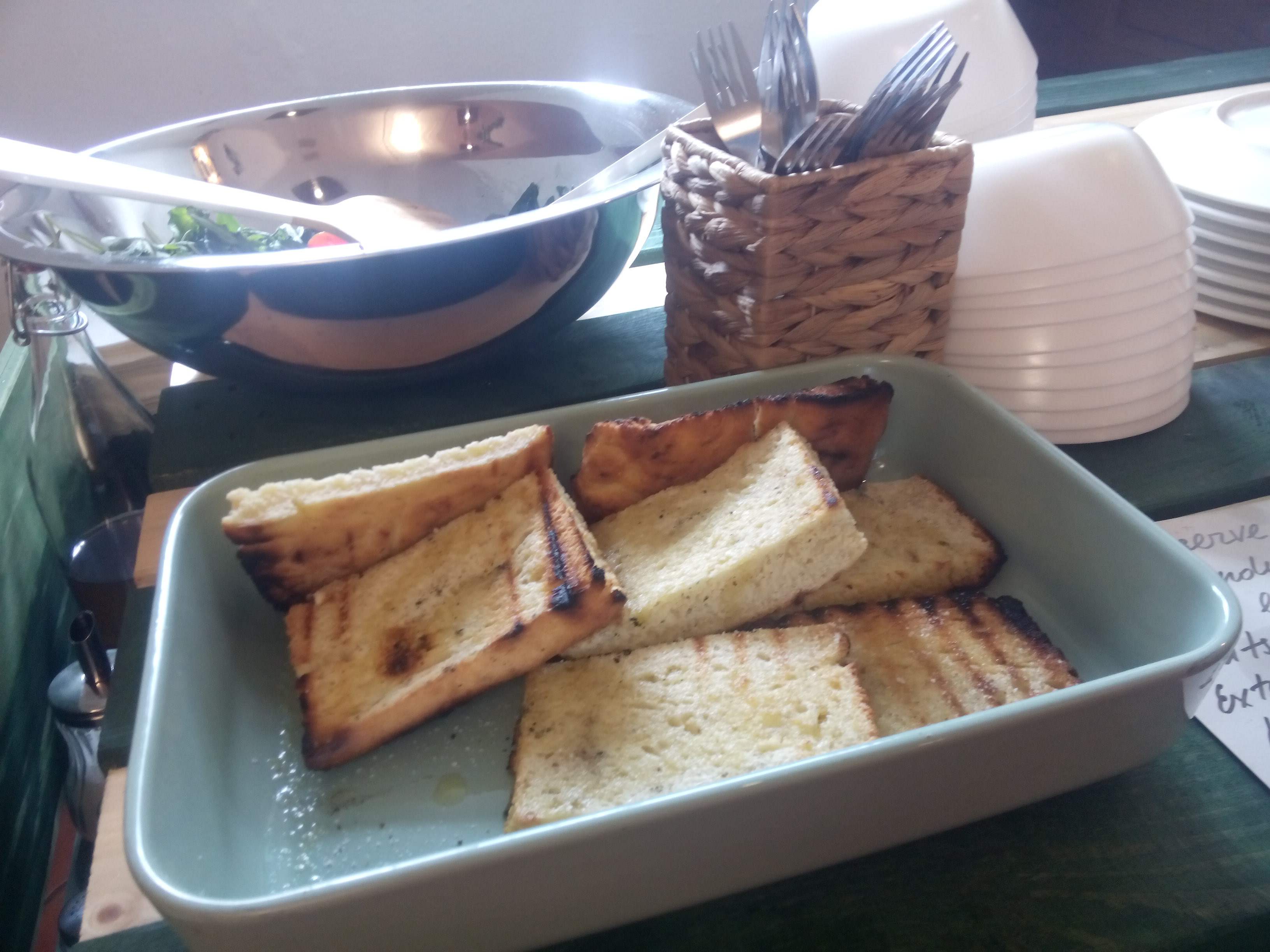 A blue tray with fat slices of ciabatta garlic bread and a silver bowl behind