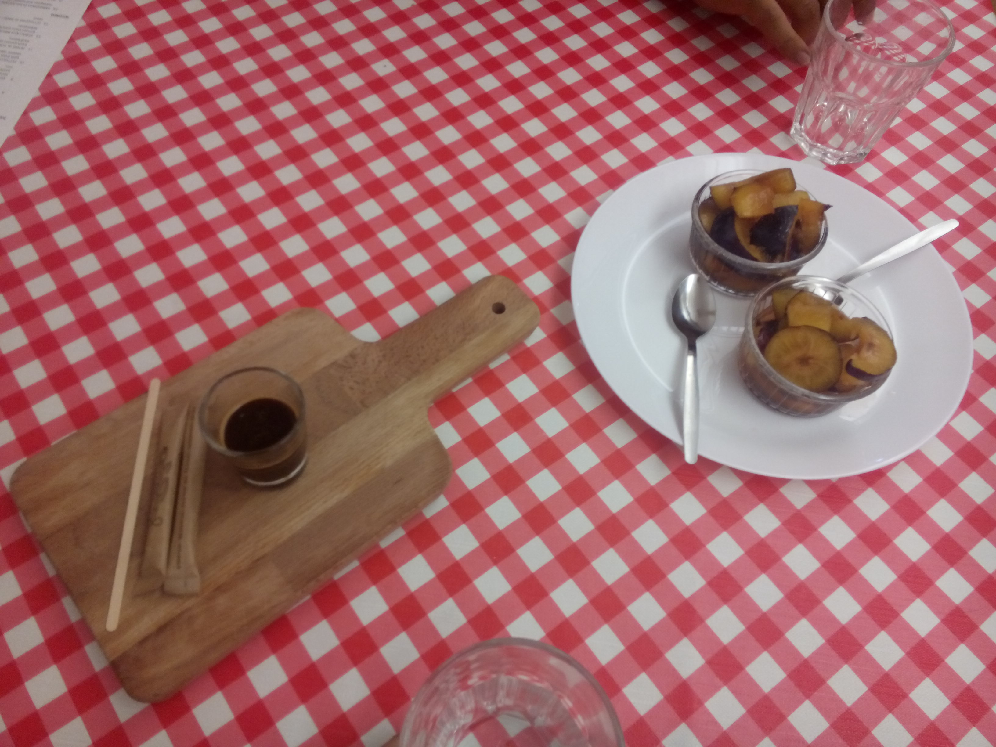 A red checkered table with a wooden paddle carrying a tiny espresso glass, alongside a white plate with two bowls of sliced plums