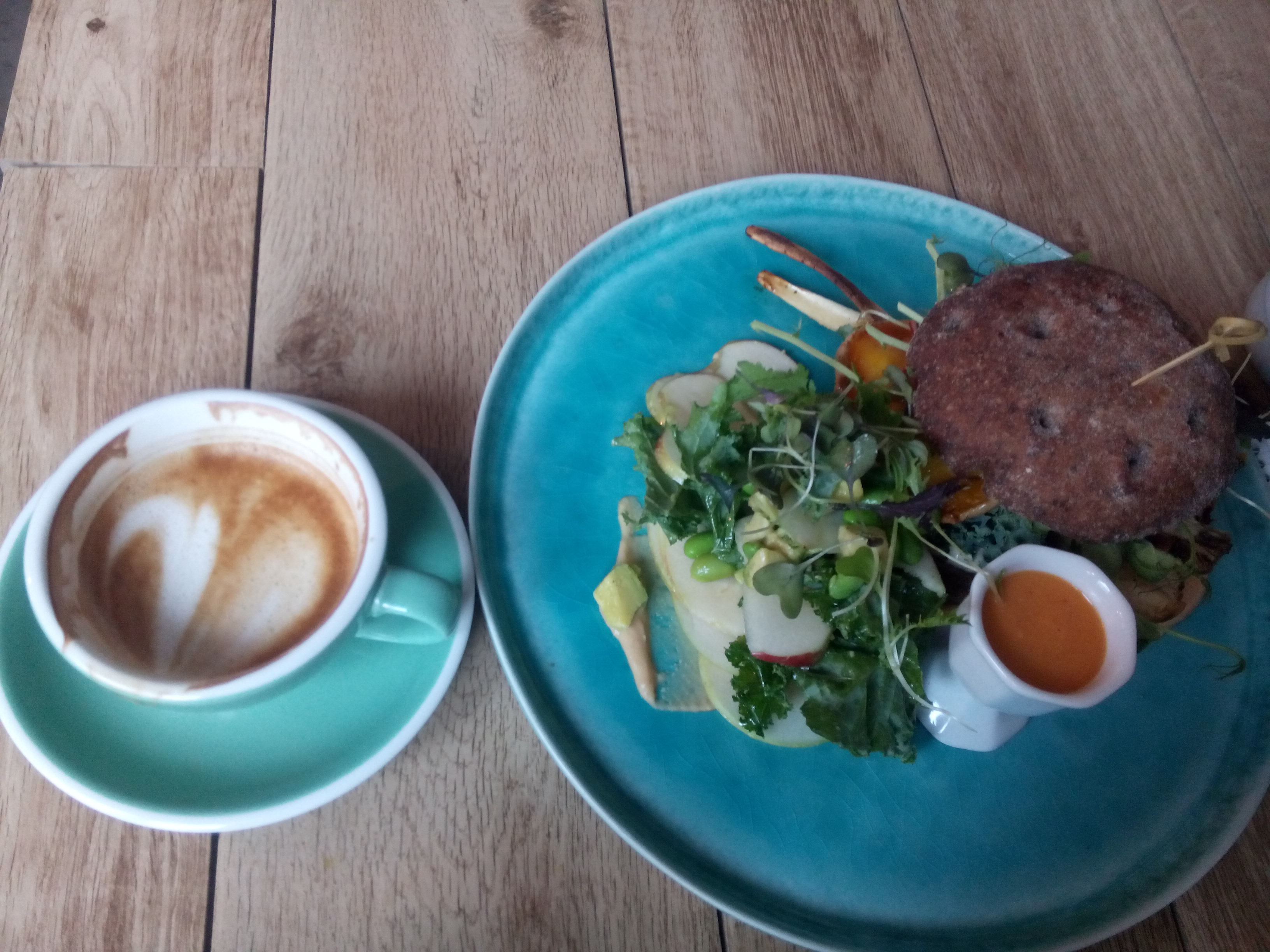 A green cup and saucer with a foamy coffee drink beside a blue plate with a pile of salad beside a burger bun and a pot of orange sauce