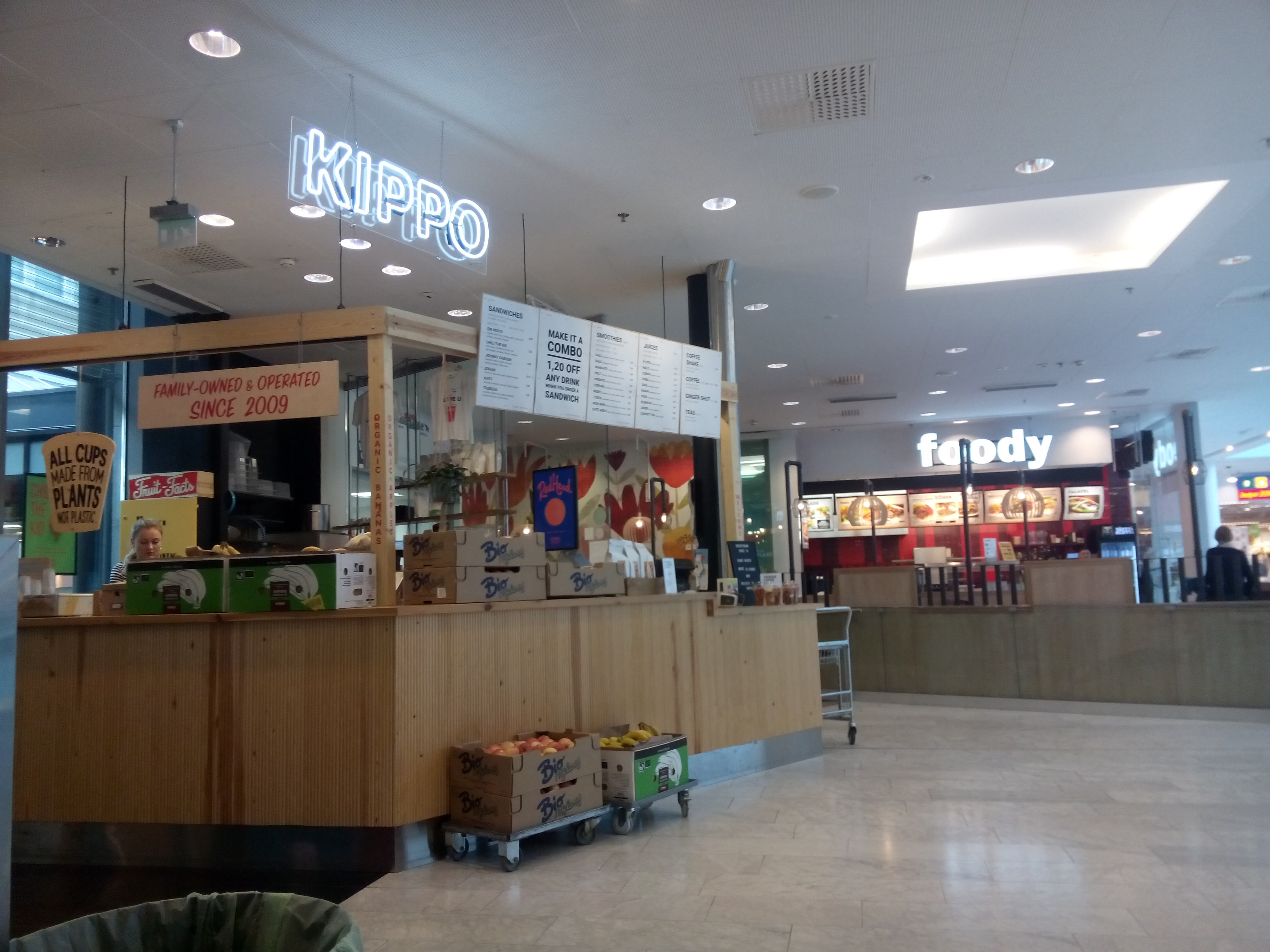 A food kiosk inside a mall with a neon sign (Kippo), wooden counter and boxes of fruit around