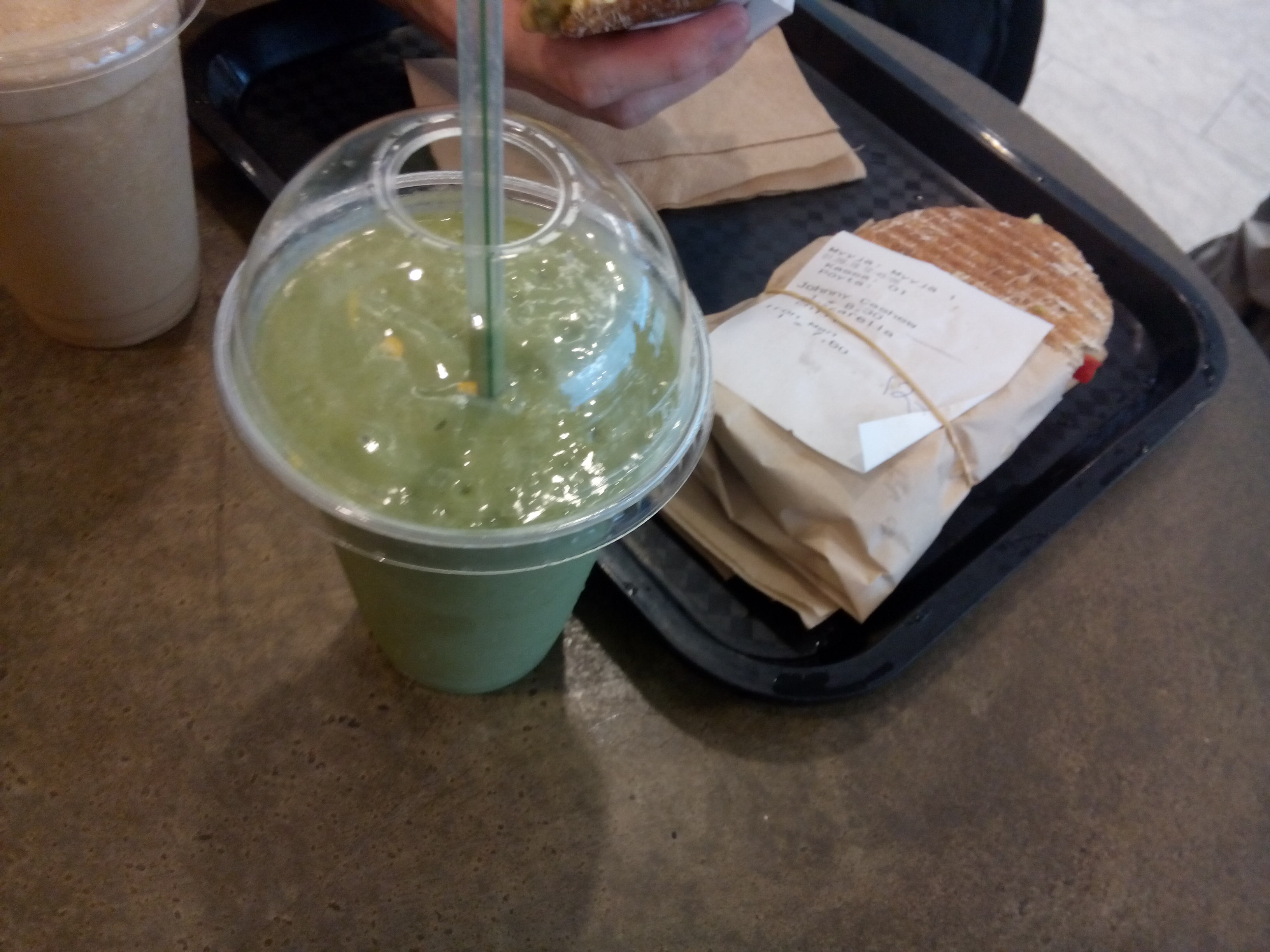 A plastic smoothie cup filled with green beside a plastic tray with a wrapped toasted sandwich