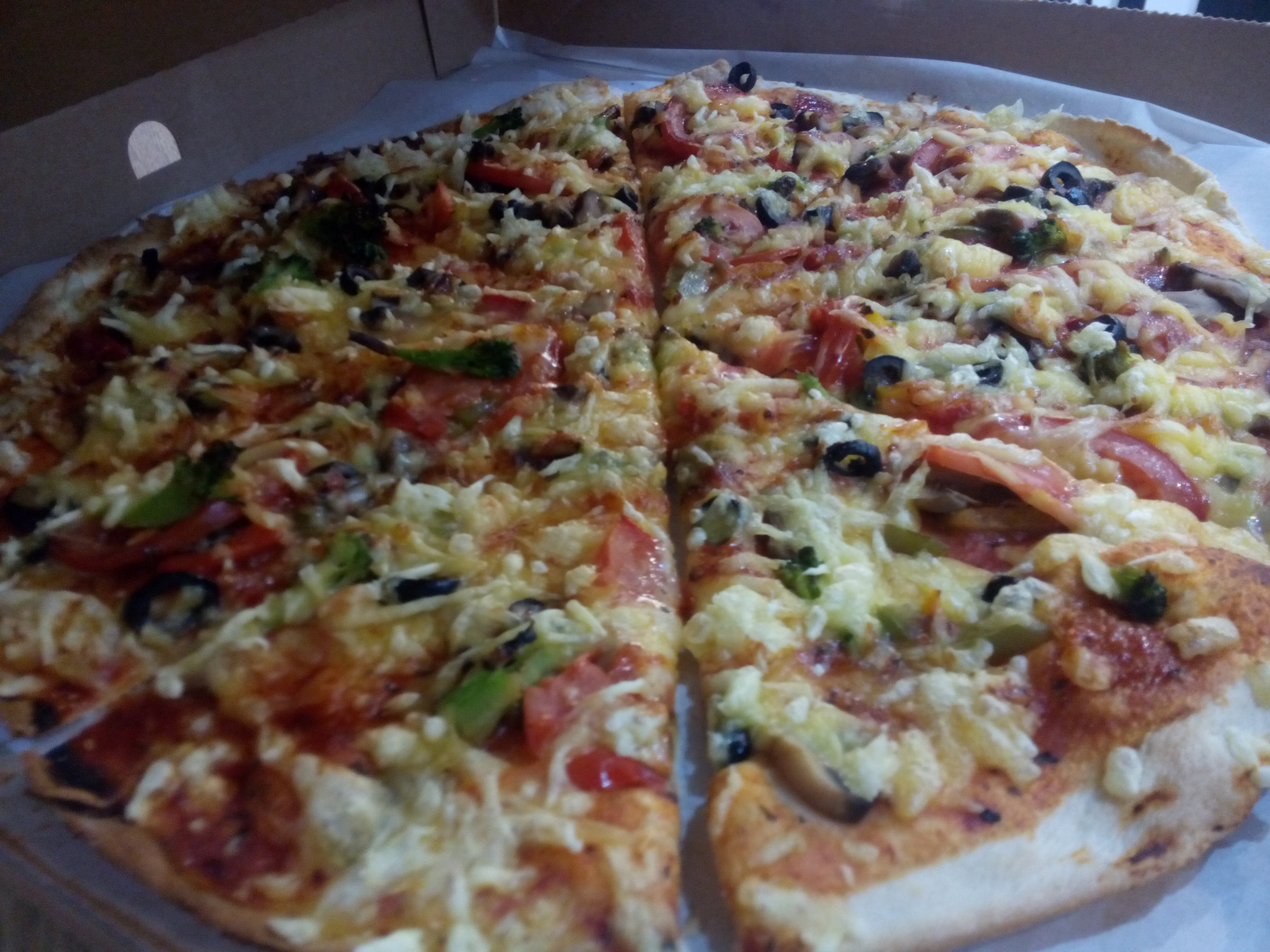 A pizza in a cardboard takeout box with vegetables and vegan cheese