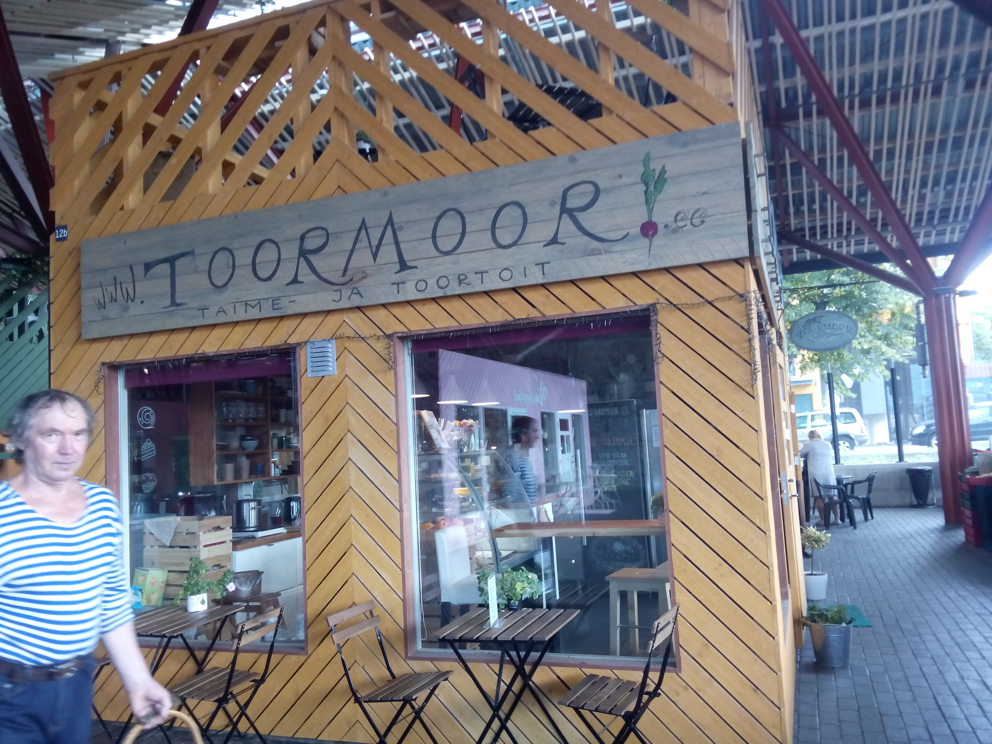 A yellow wooden panelled hut with a handpainted 'Toormoor' sign, large windows and some seats outside