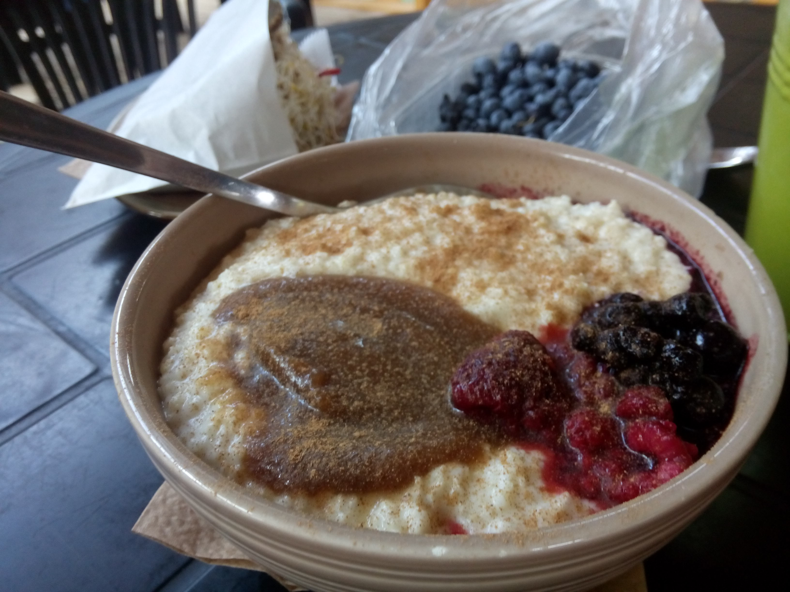 A bowl of porridge, with red and black berries, caramely sauce and cinnamon