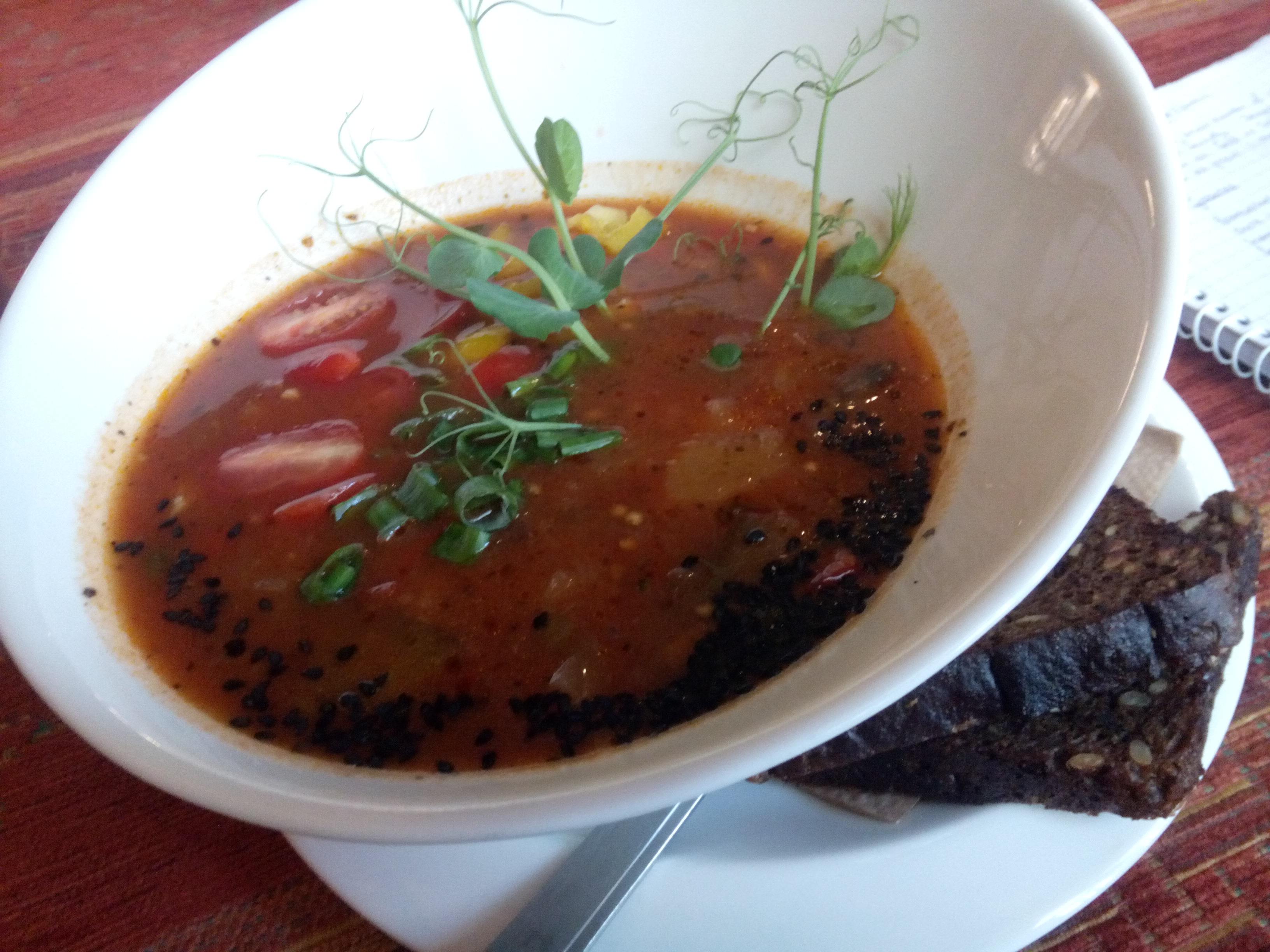 A white bowl with red soup and green garnish, with black bread on the side
