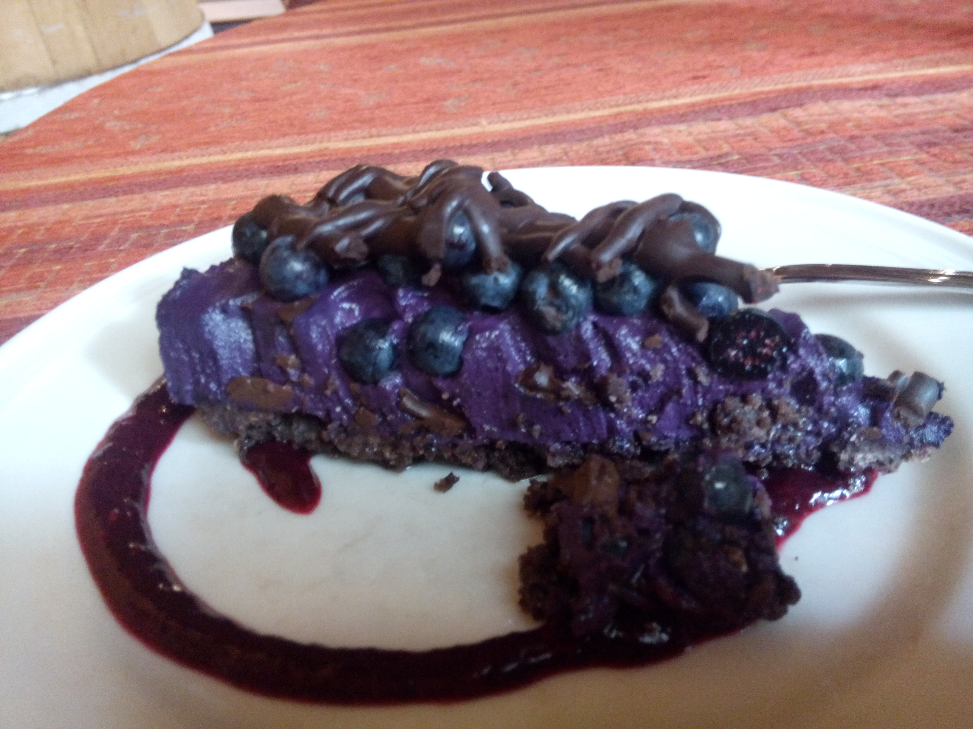 A purple and chocolate cake on a white plate with pink sauce drizzled