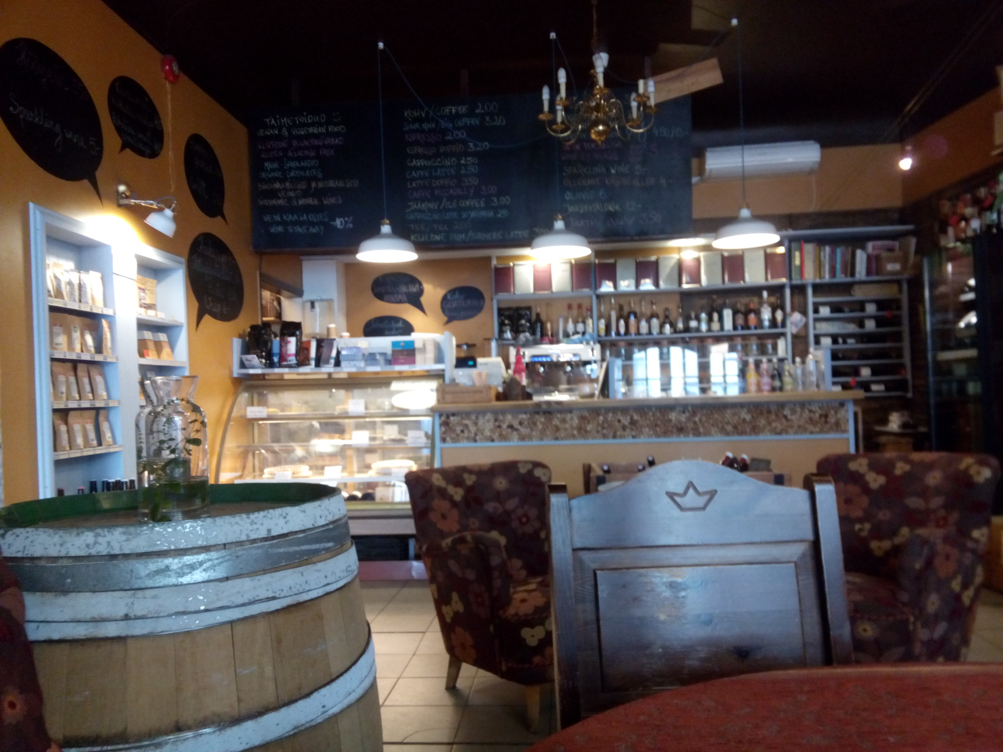 A cafe interior with wooden chairs and barrels, red armchairs and a counter in teh background with shelves filled with delcious things
