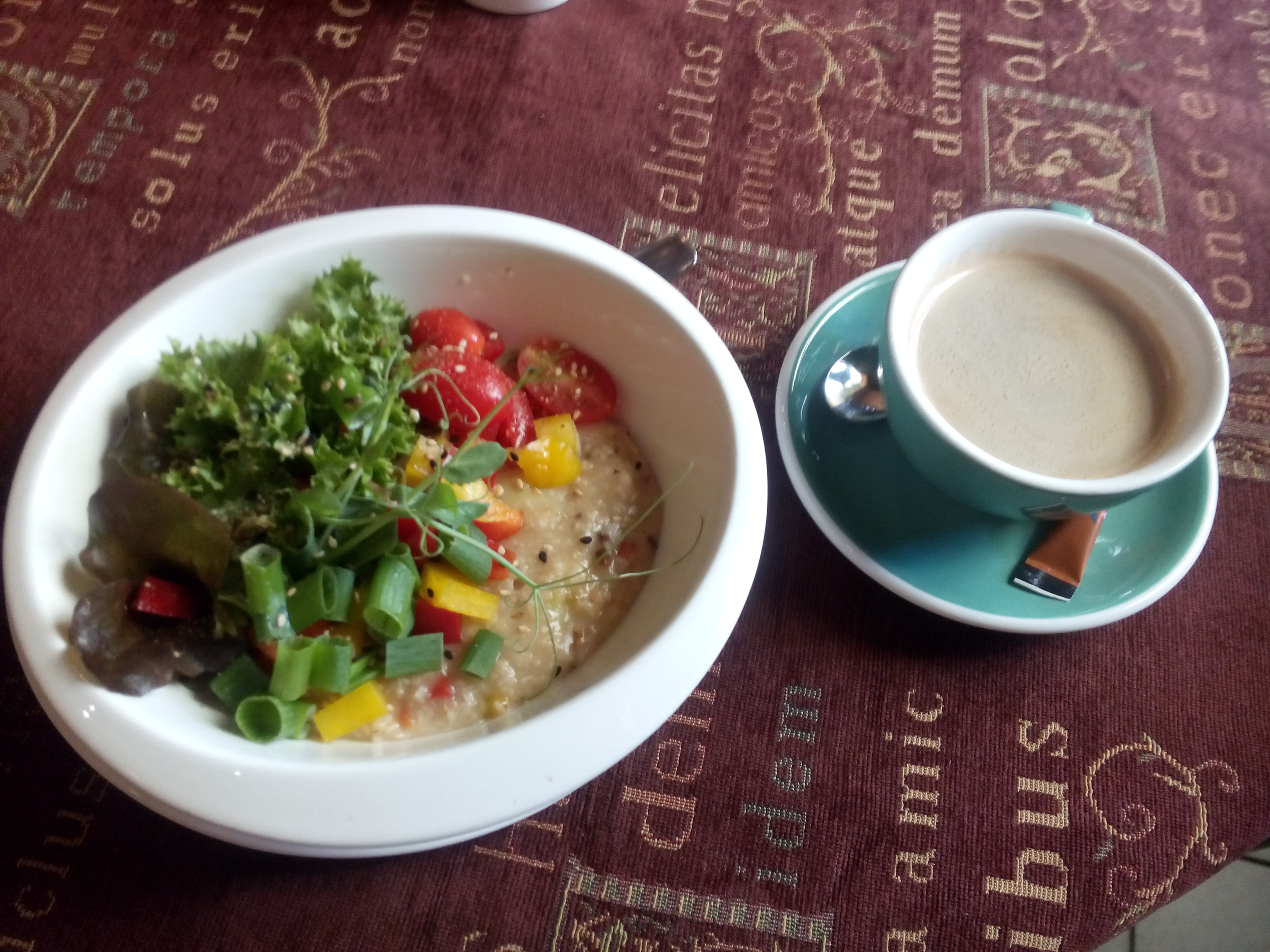 A red and gold tablecloth underneath a bowl of porridge with greens and tomatos, and a blue cup and saucer with coffee