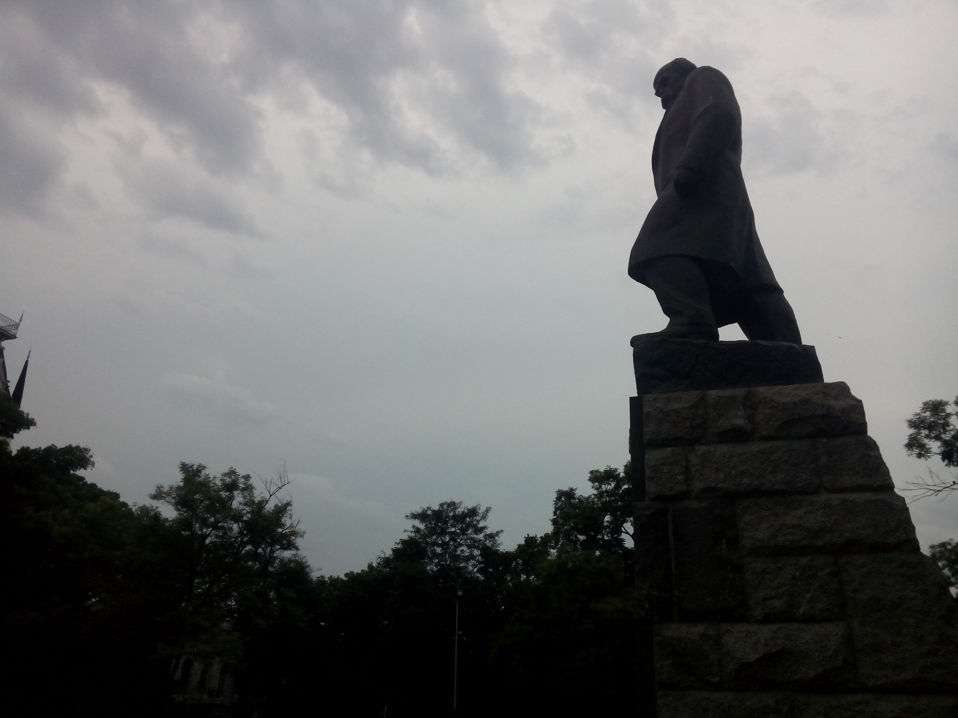 A silhouette of a tall statue of a man from the side