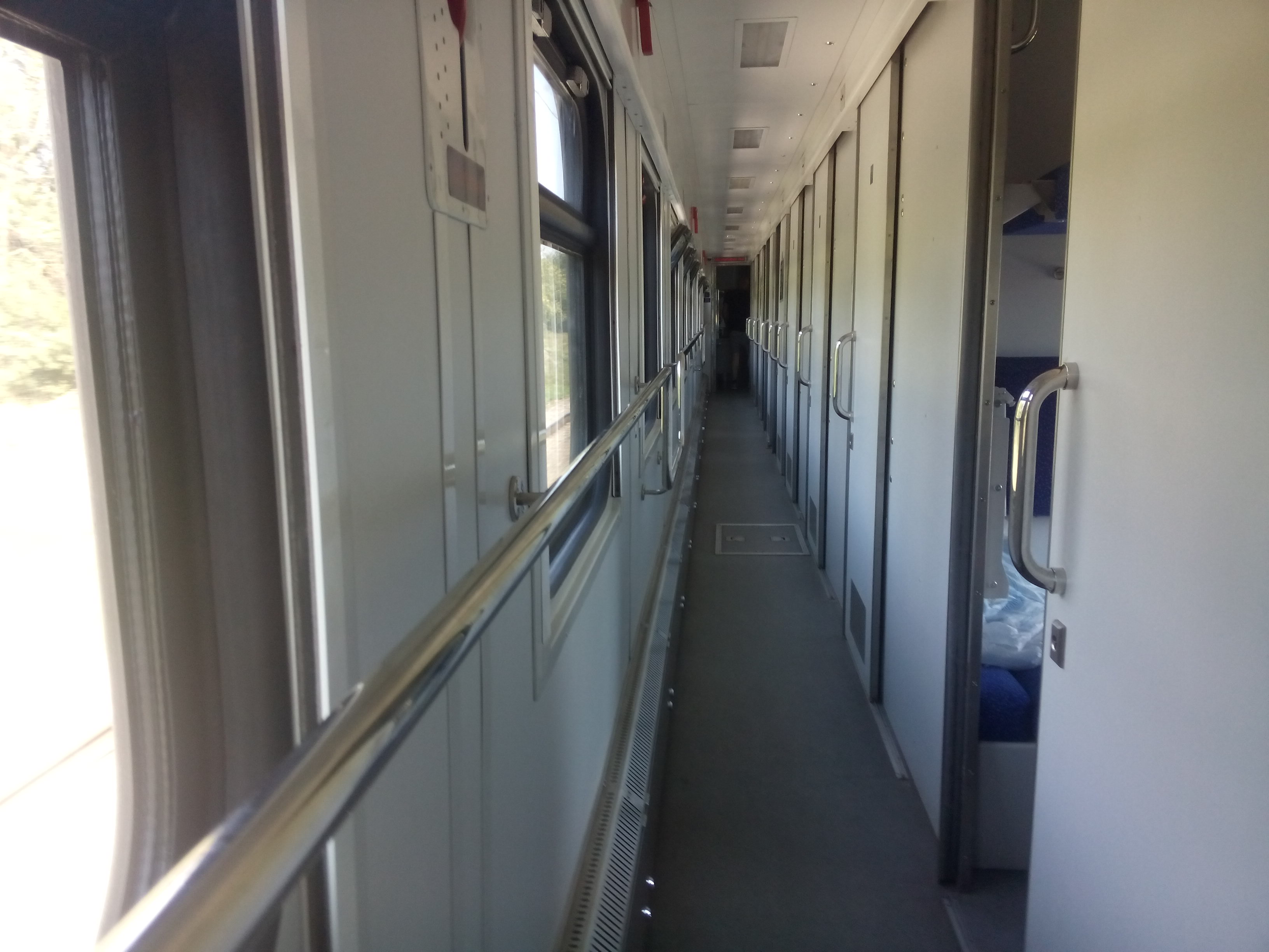 A narrow corridor inside a train, with windows on the left and doors to compartments on the right