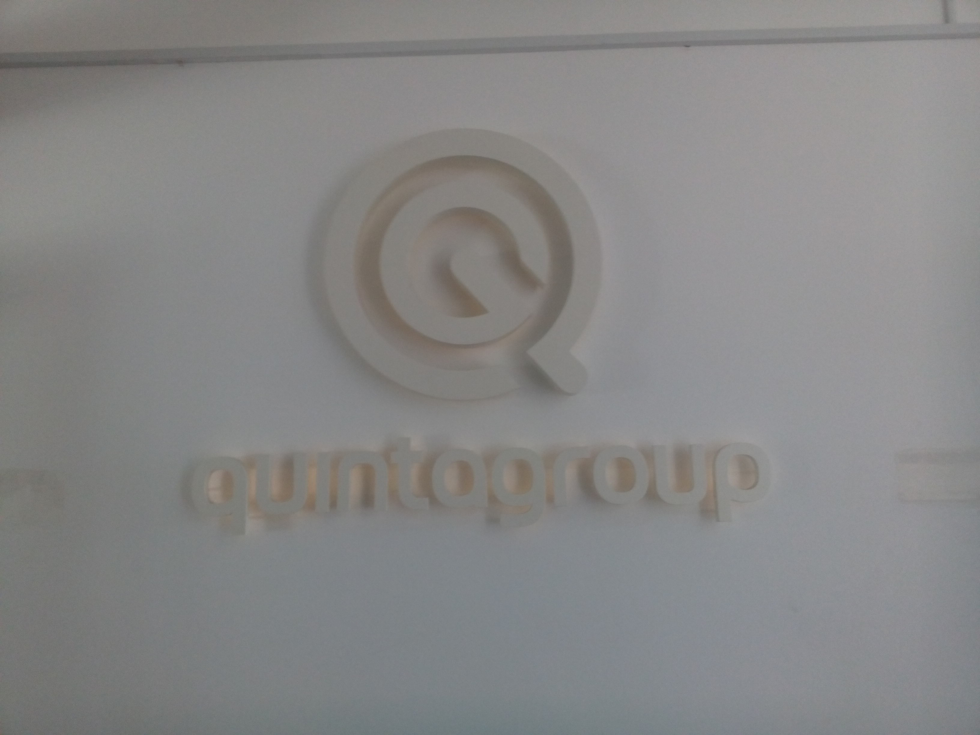 A white sign on a white wall saying 'quintagroup'