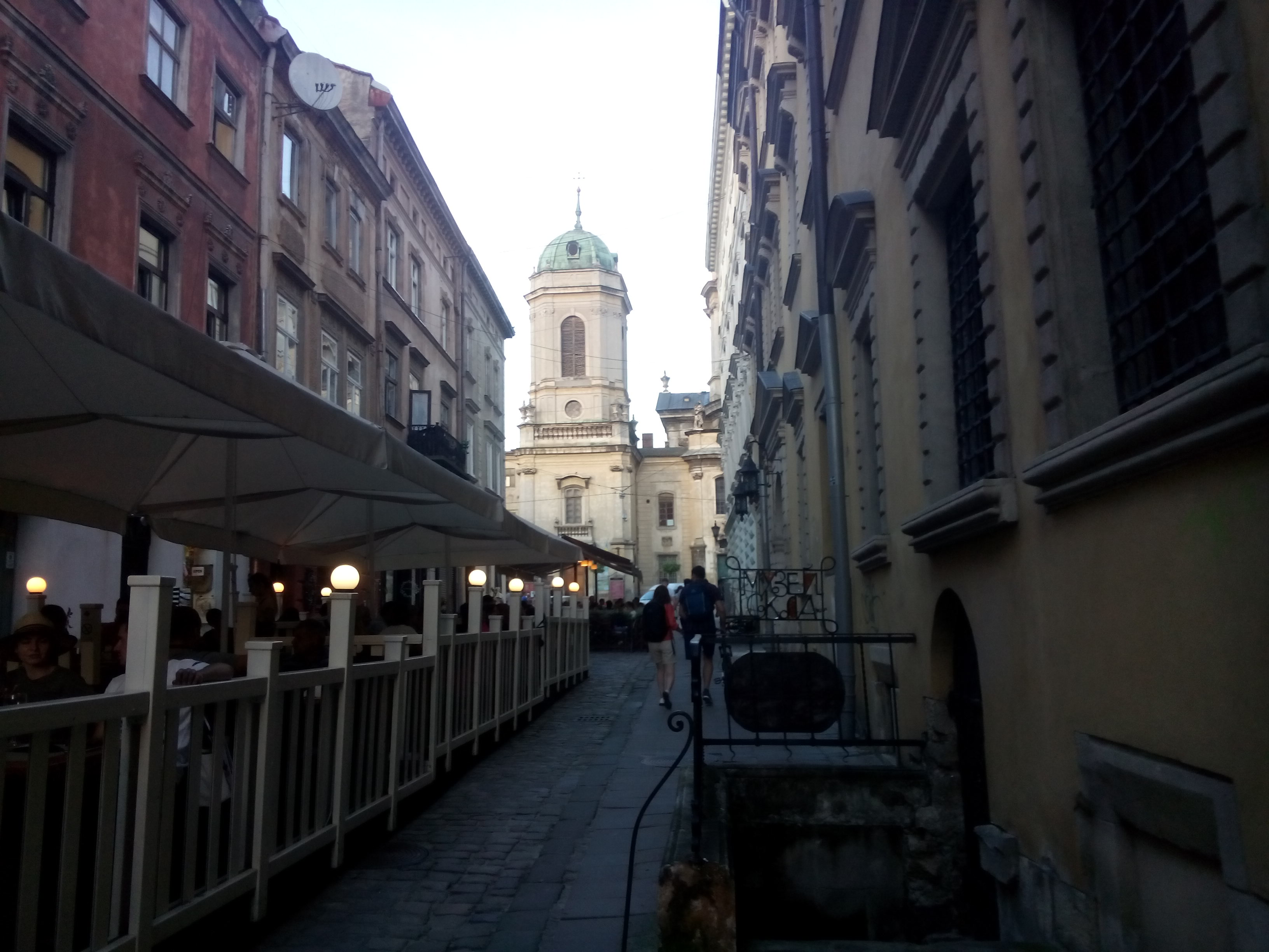 A narrow cobbled street with restaurant tables to the left and a domed church at the far end