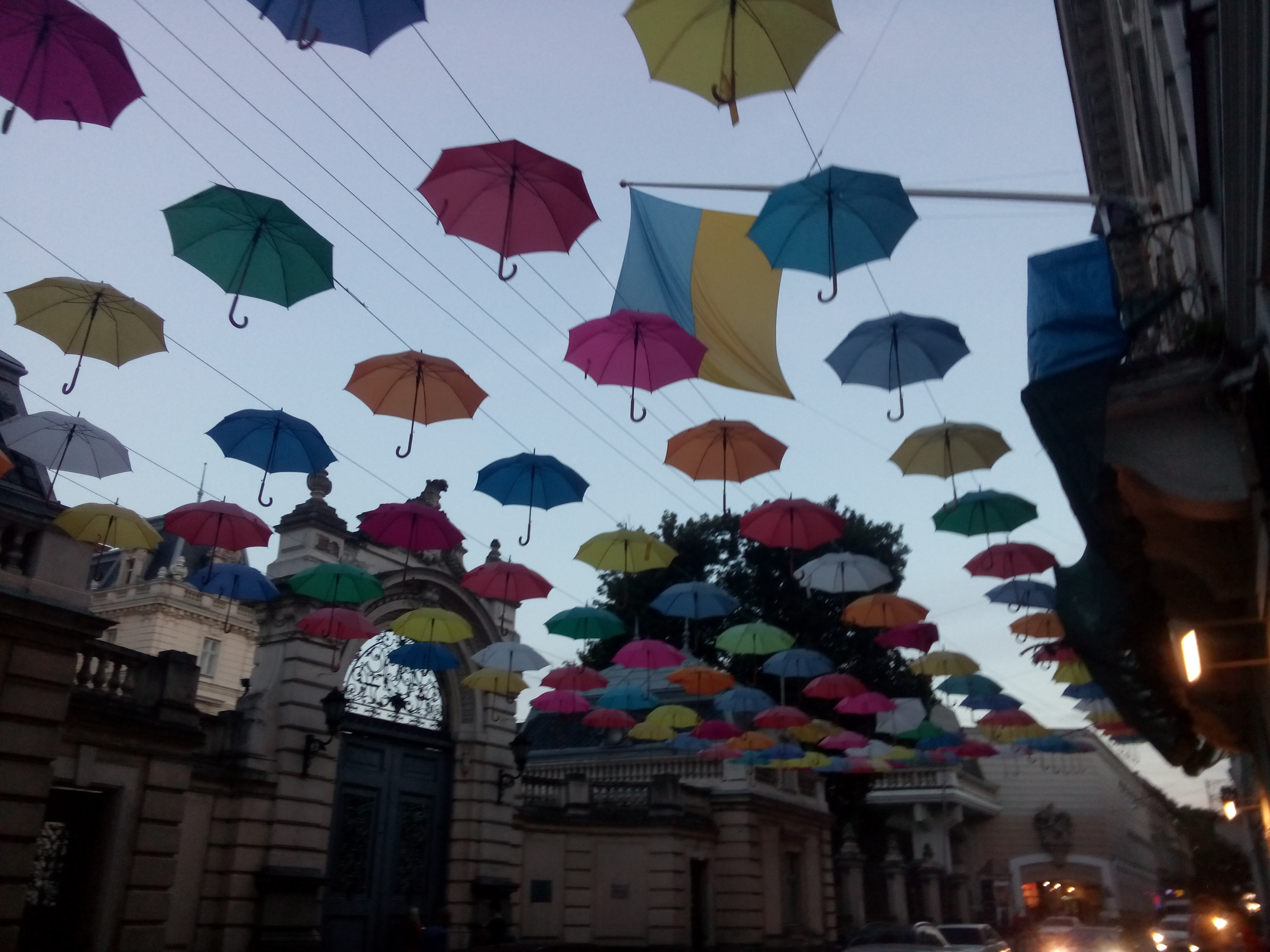 Dozens of bright coloured umbrellas strung up over a street