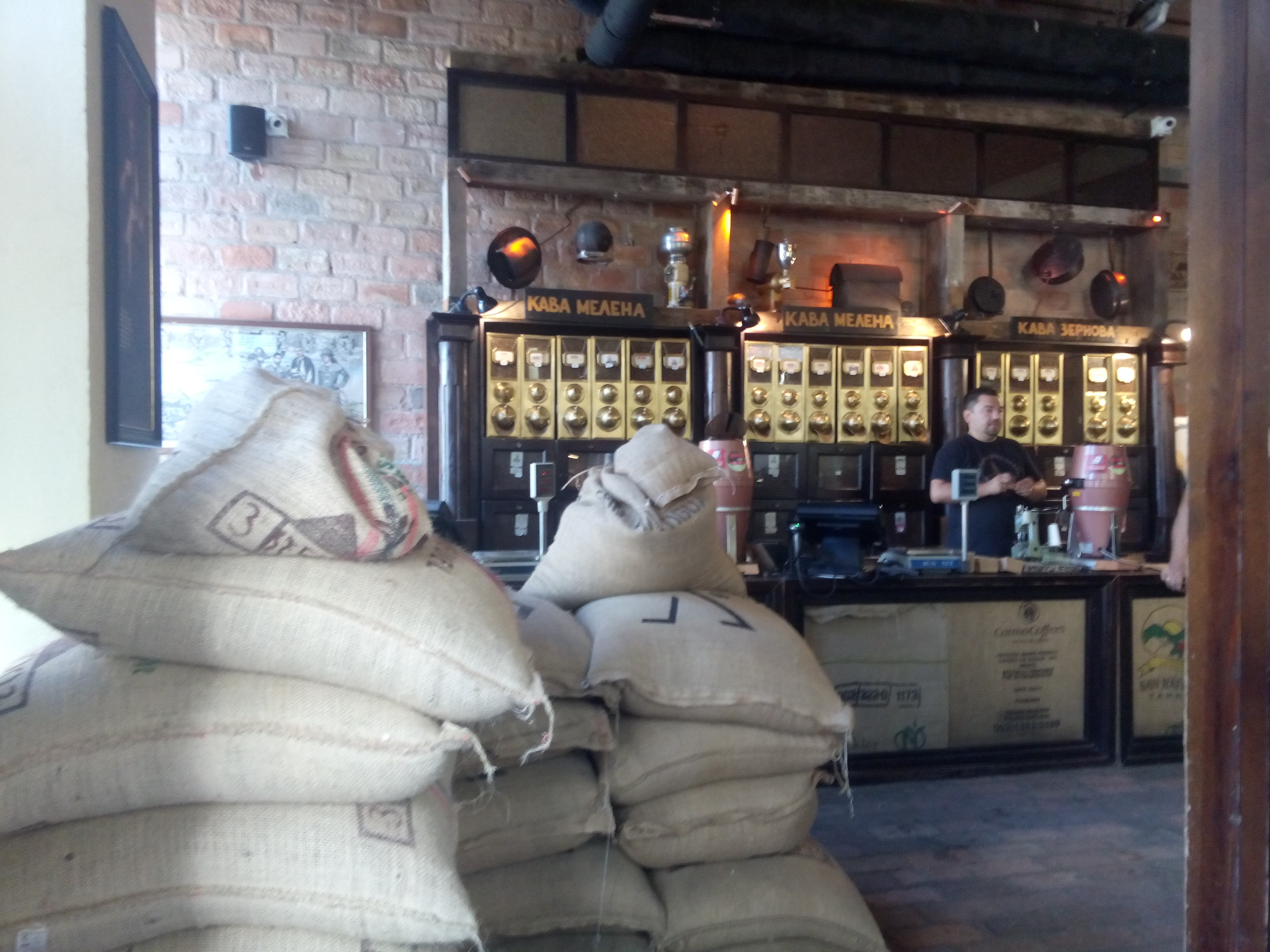 Sacks of coffee beans in the foreground and coffee grinding machines against a brick wall in the background