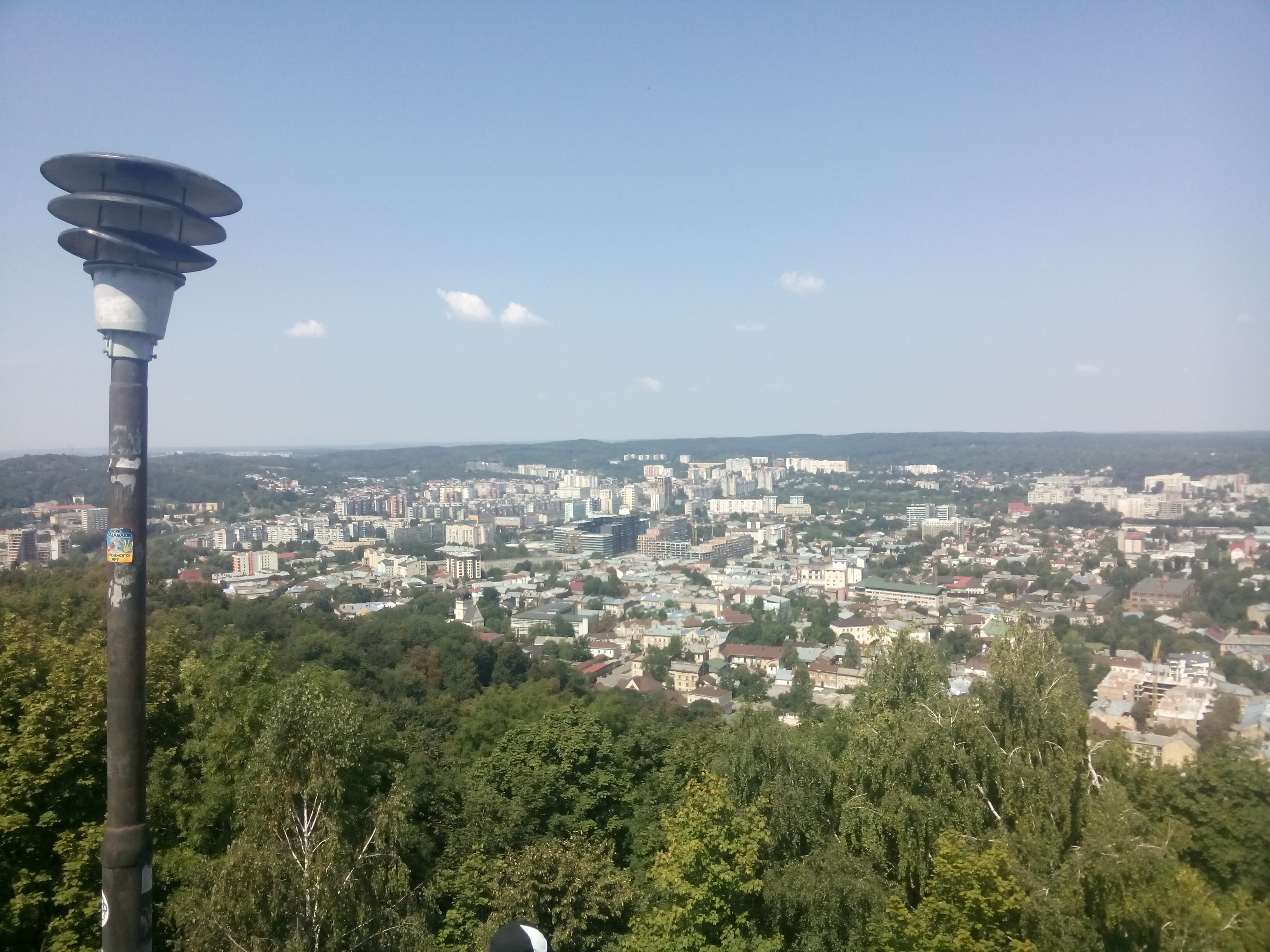 A lamp in the foreground of a view over Lviv from high up