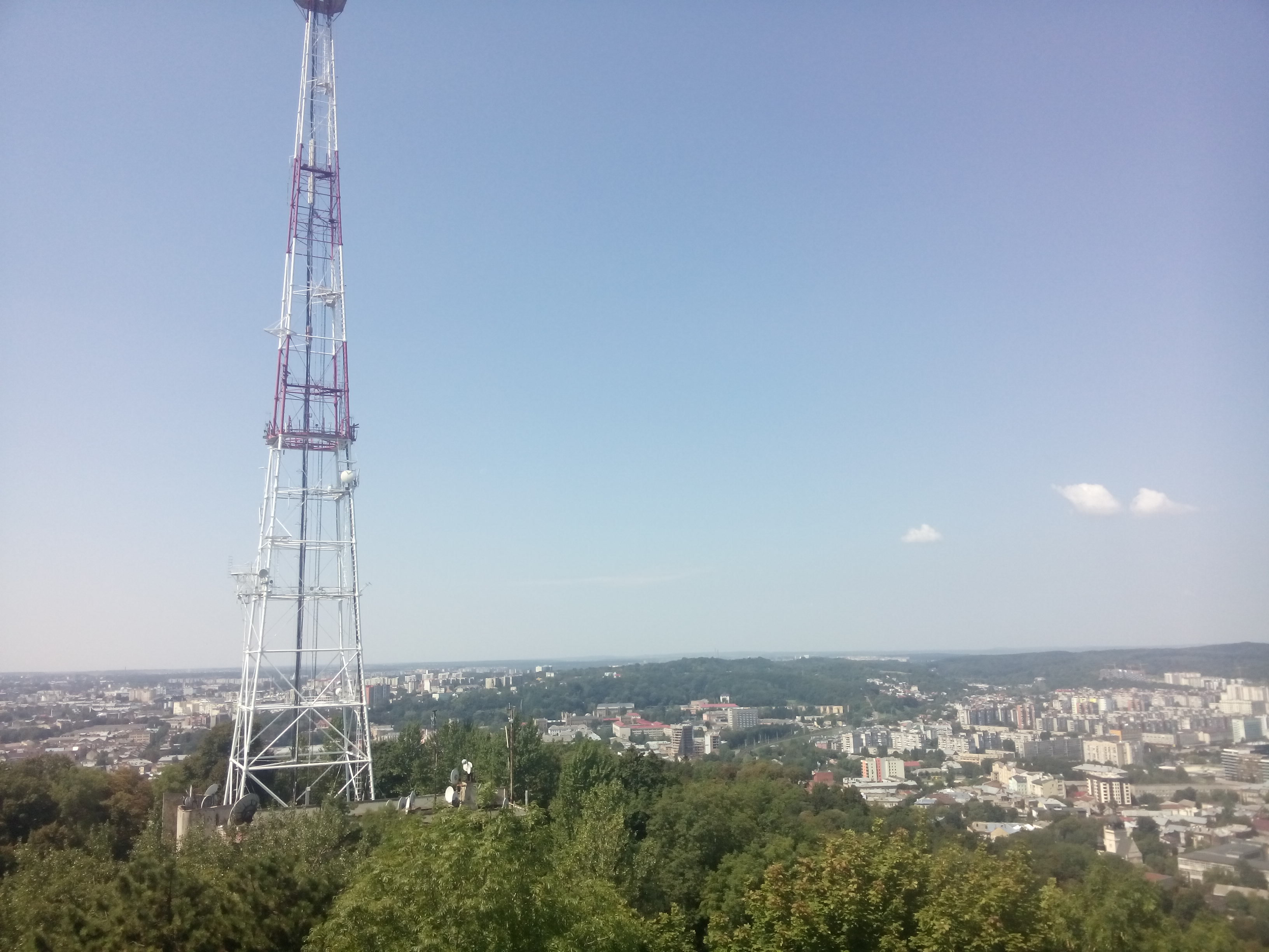 A view over Lviv from high up, with trees and a TV tower