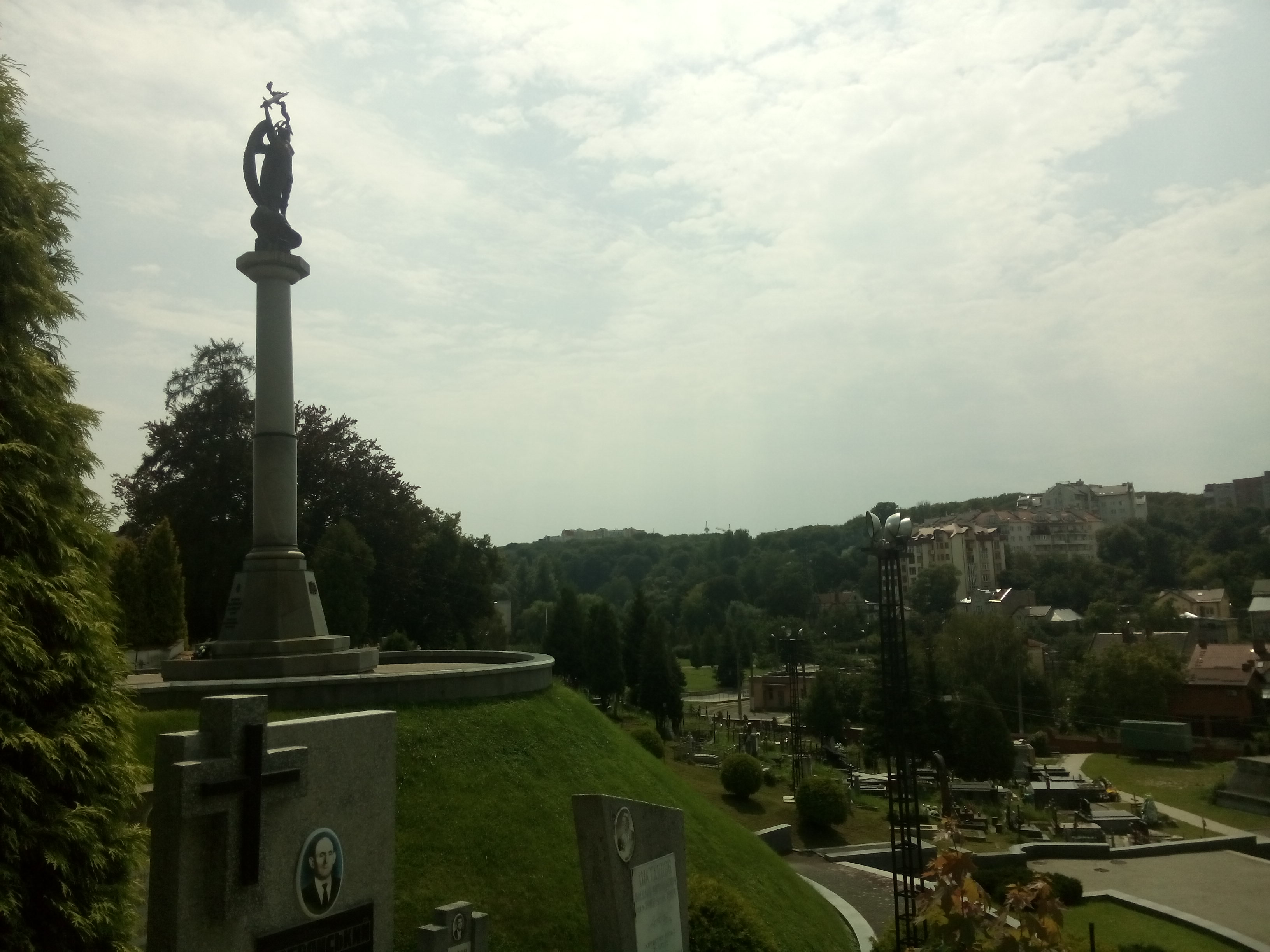 A monument on a hill to the left and grass and well maintained graves