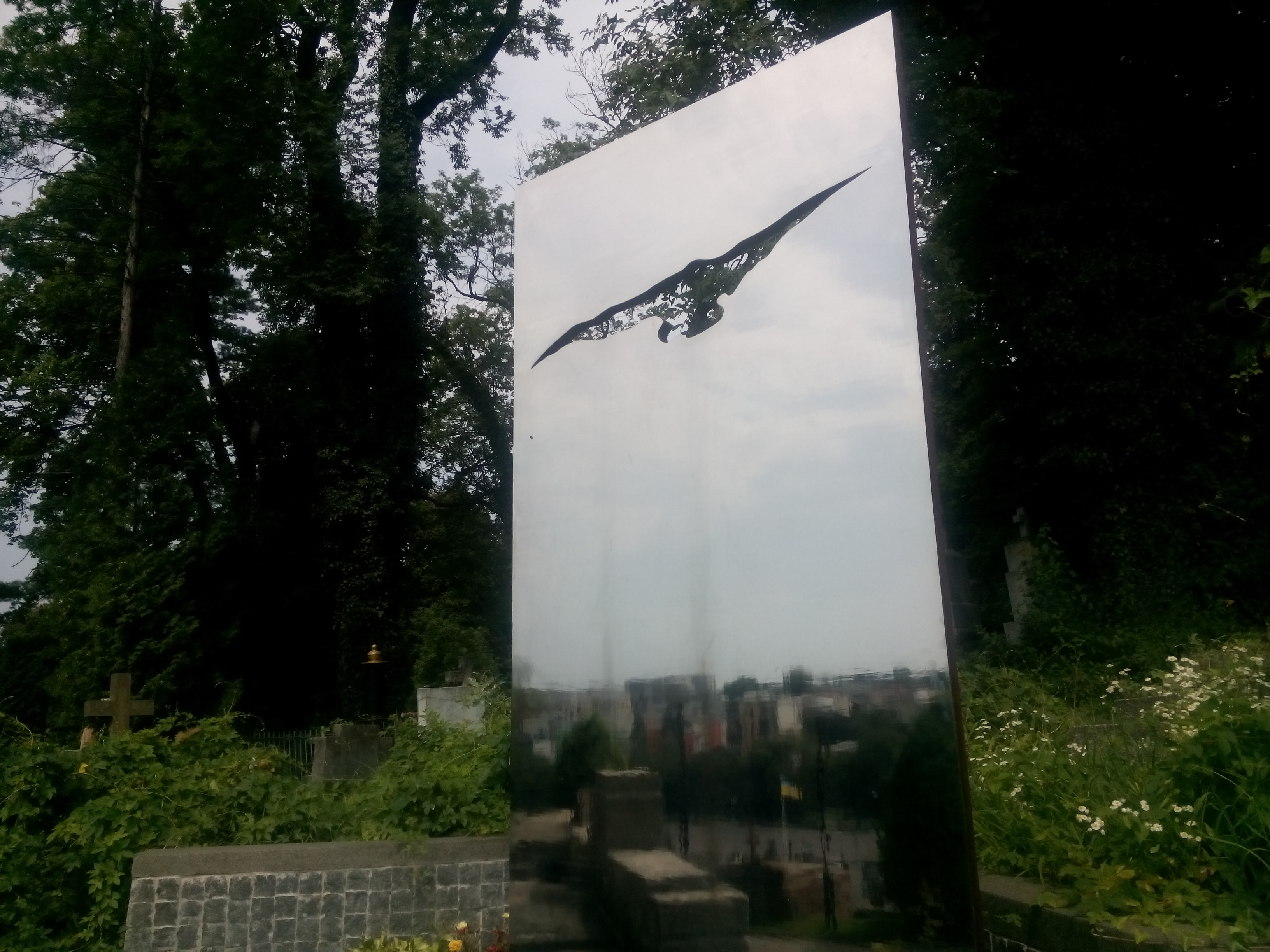 A headstone made from reflective metal with a flying bird carved out, amongst the bushes