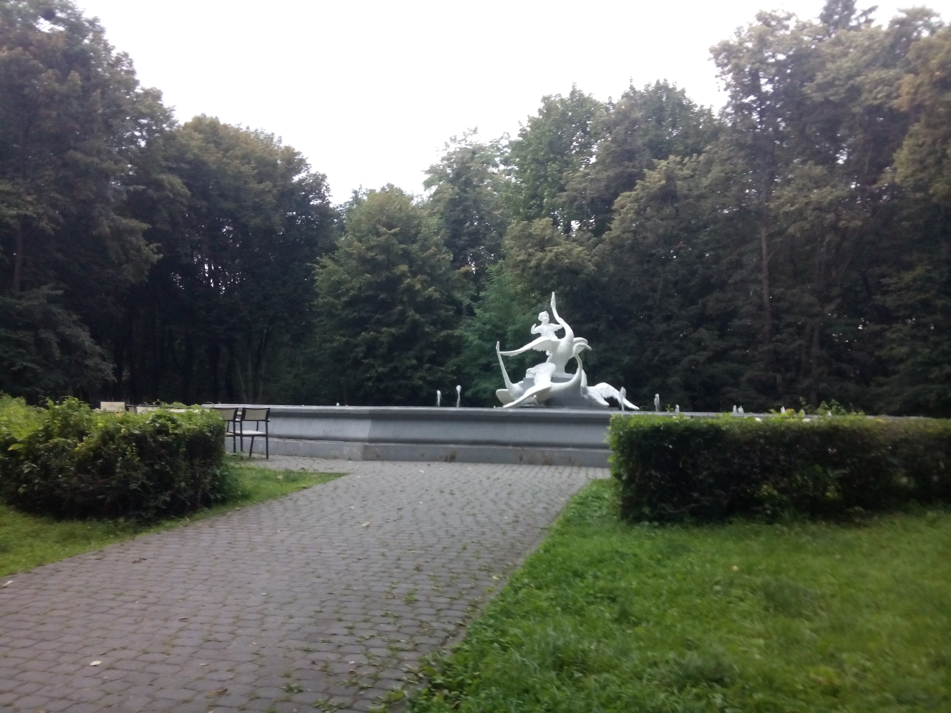A cobbled path leads to a bright white elaborate swan fountain, with trees in the background, but no water