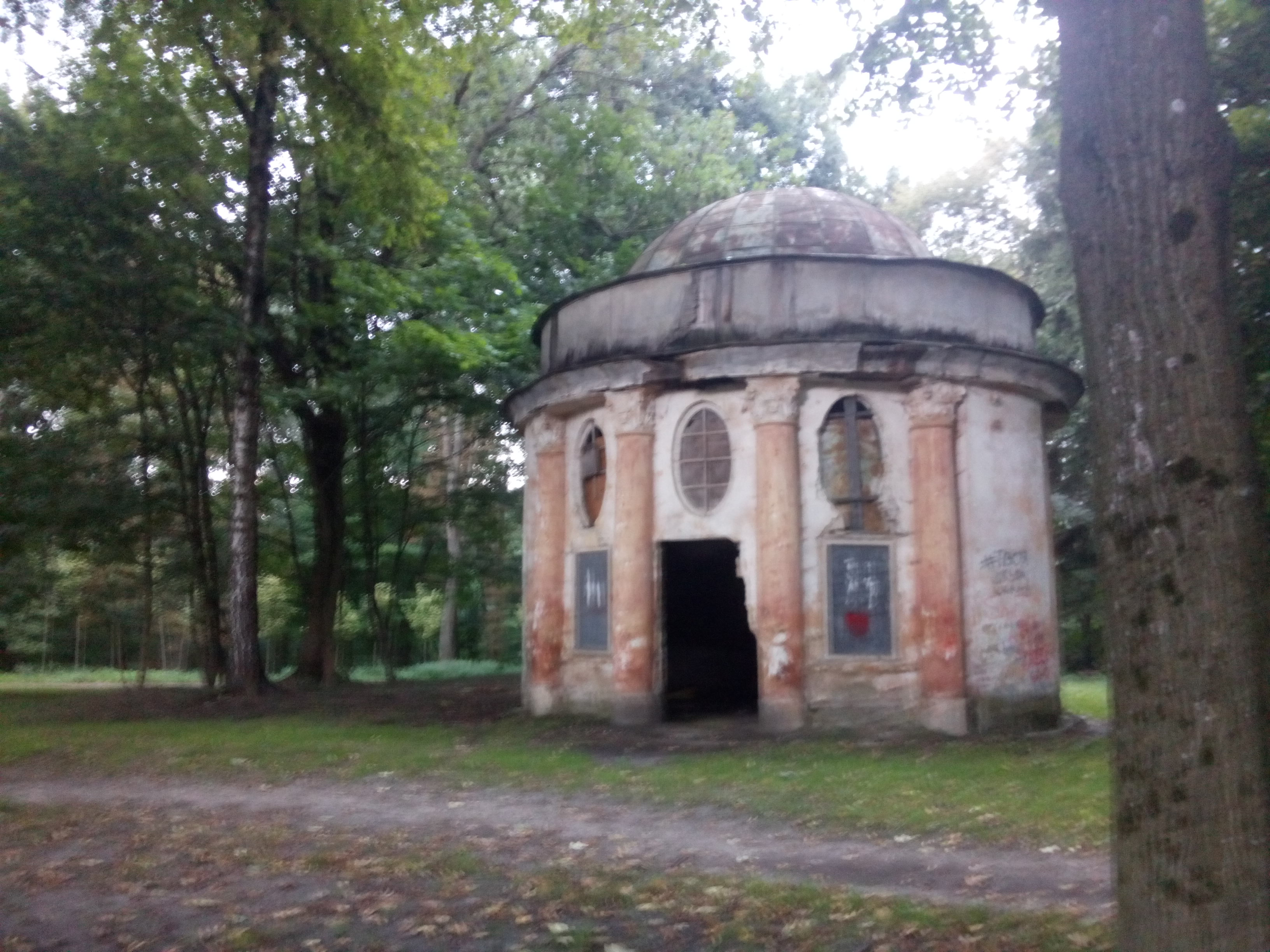 Round derelict building with a domed roof amongst the trees