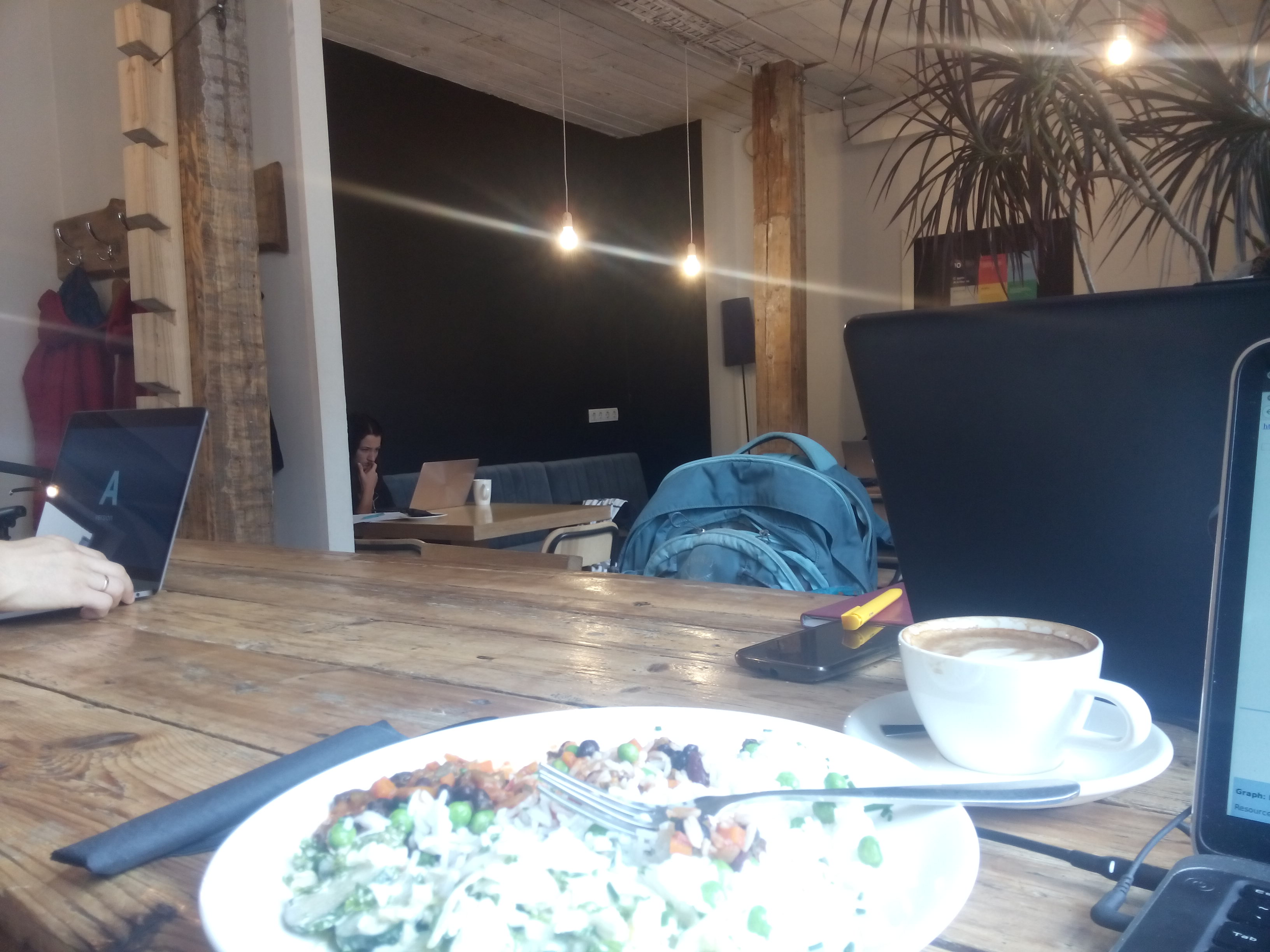 A wooden table bears a plate of chilli and rice beside a foamy latte. In the background is a hipster cafe with lights on long strings, wooden beams and people with laptops