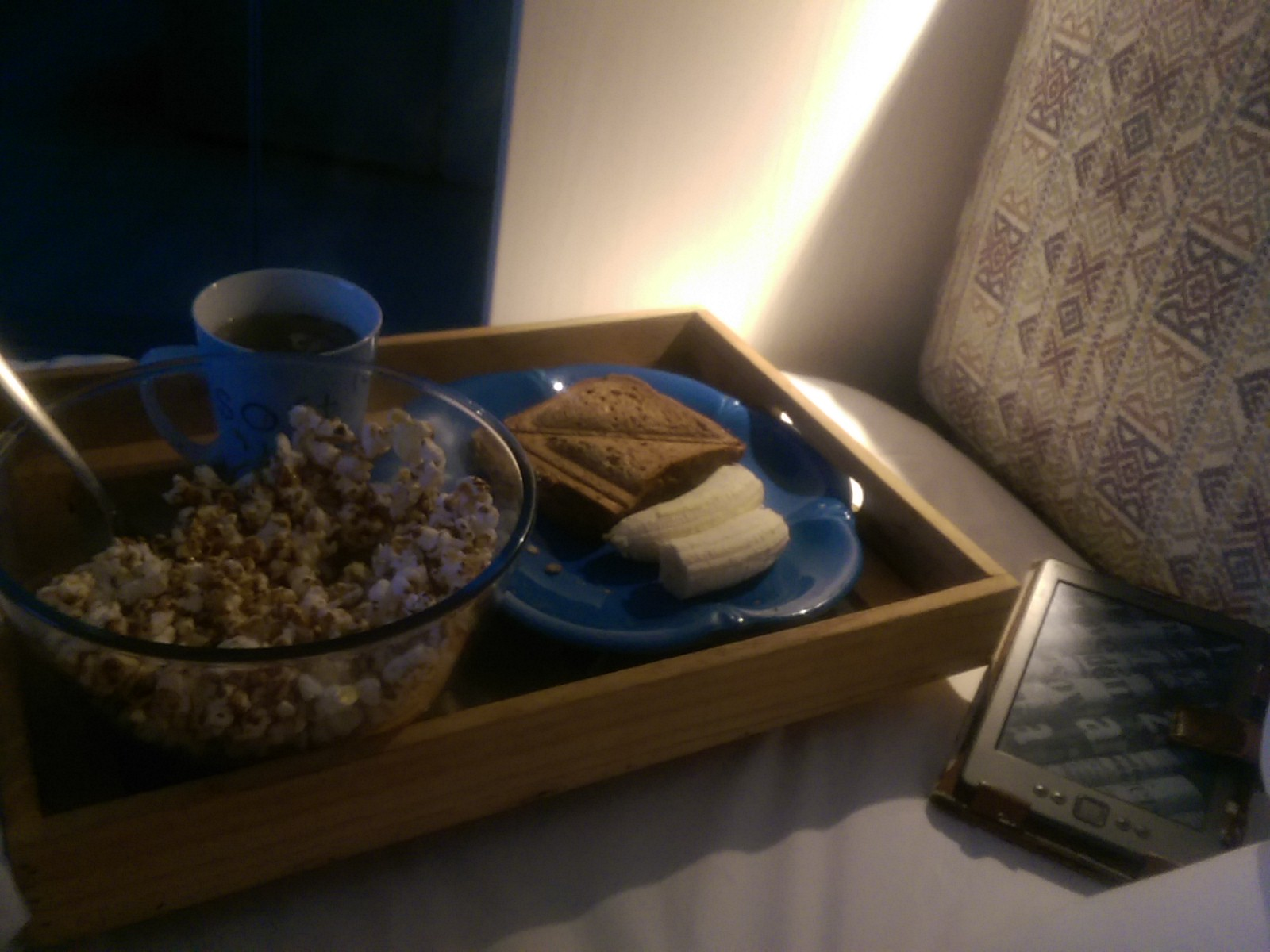 A tray on a bed with a blue plate with a sandwich, a cup, and a bowl of popcorn