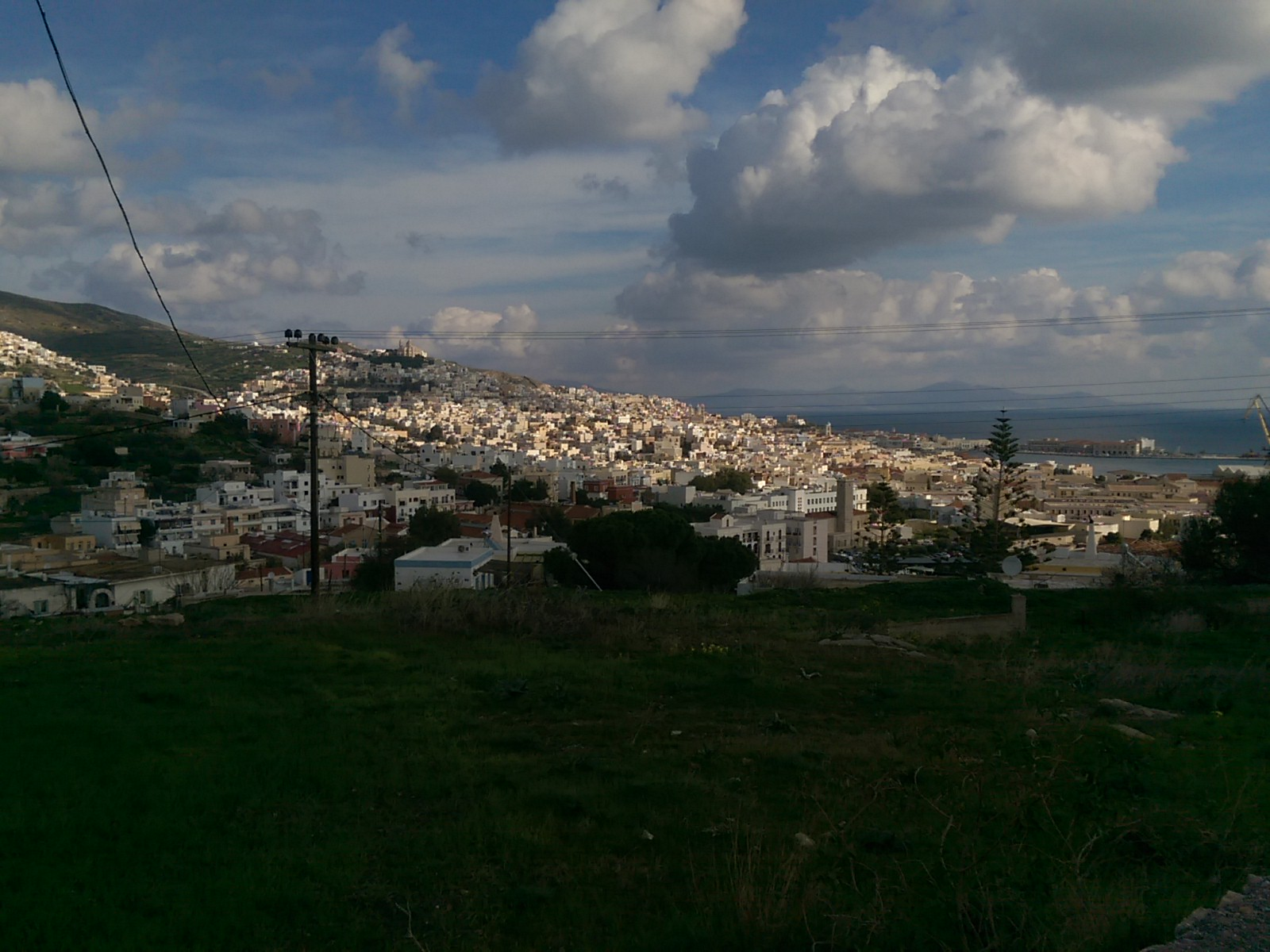 Fluffy white clouds in a blue sky; green grass in the foreground; a sprawling white town over hills, by the sea