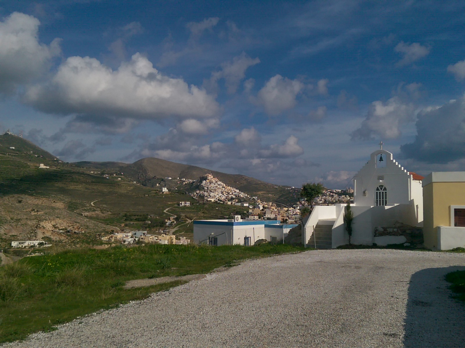A concrete road leads to a small white church with a bell; hills in the distance are half green, half covered white a white town