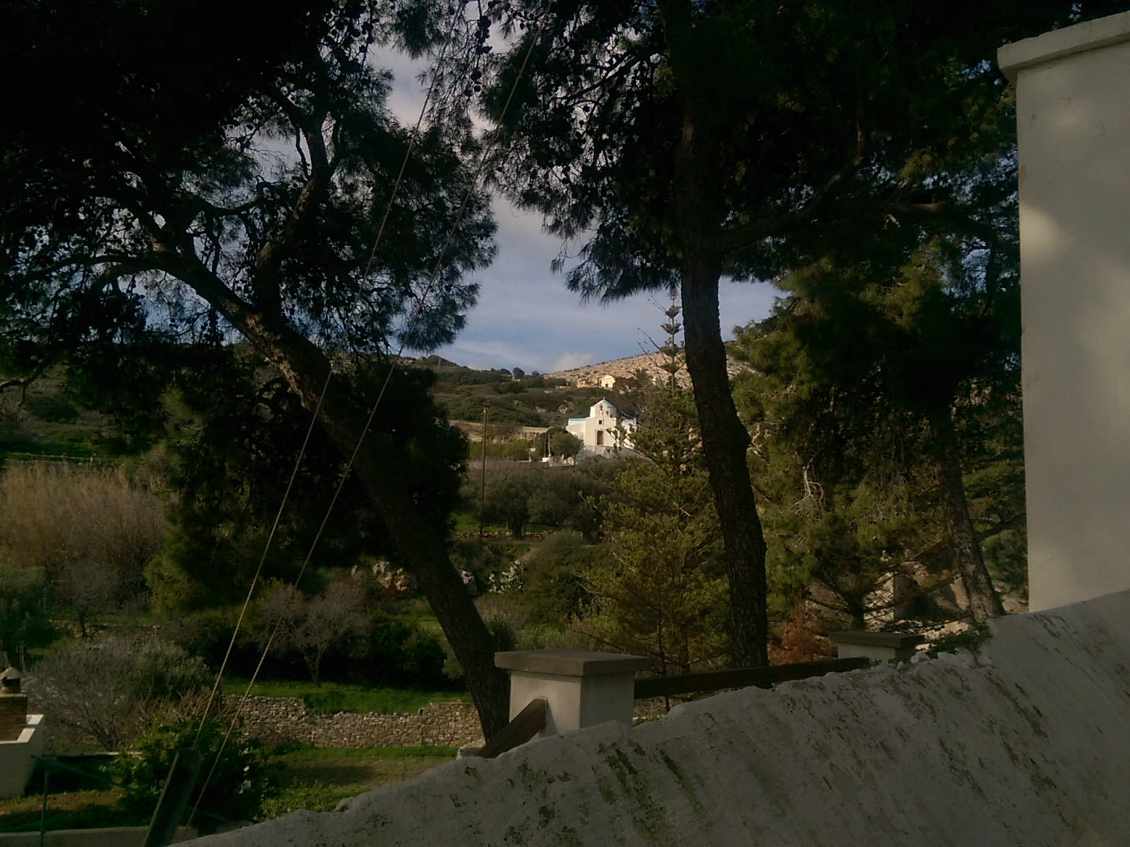 A view between two trees shows a distant white chapel