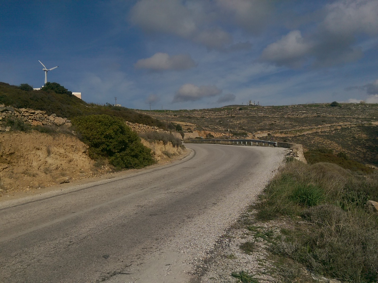 A concrete road curves around to the left, with gorse on both sides, a blue sky and a wind turbline in the distance