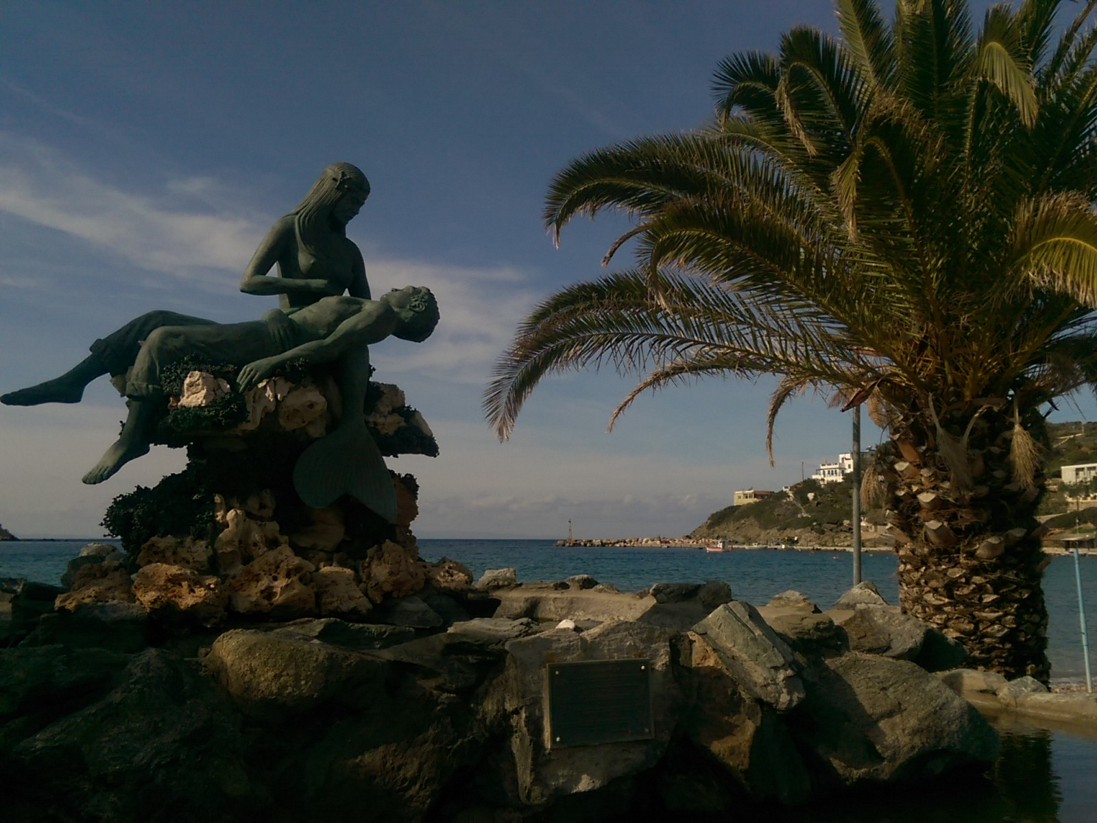 A green statue of a mermaid holding a man beside a palm tree with blue sea in the background