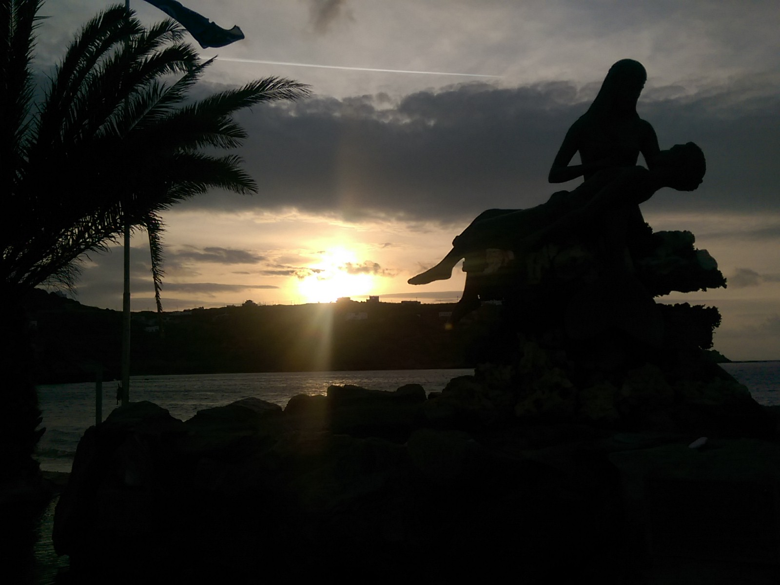 The silhouette of a statue of a woman holding a man in front of a pale orange sunset over the ocean