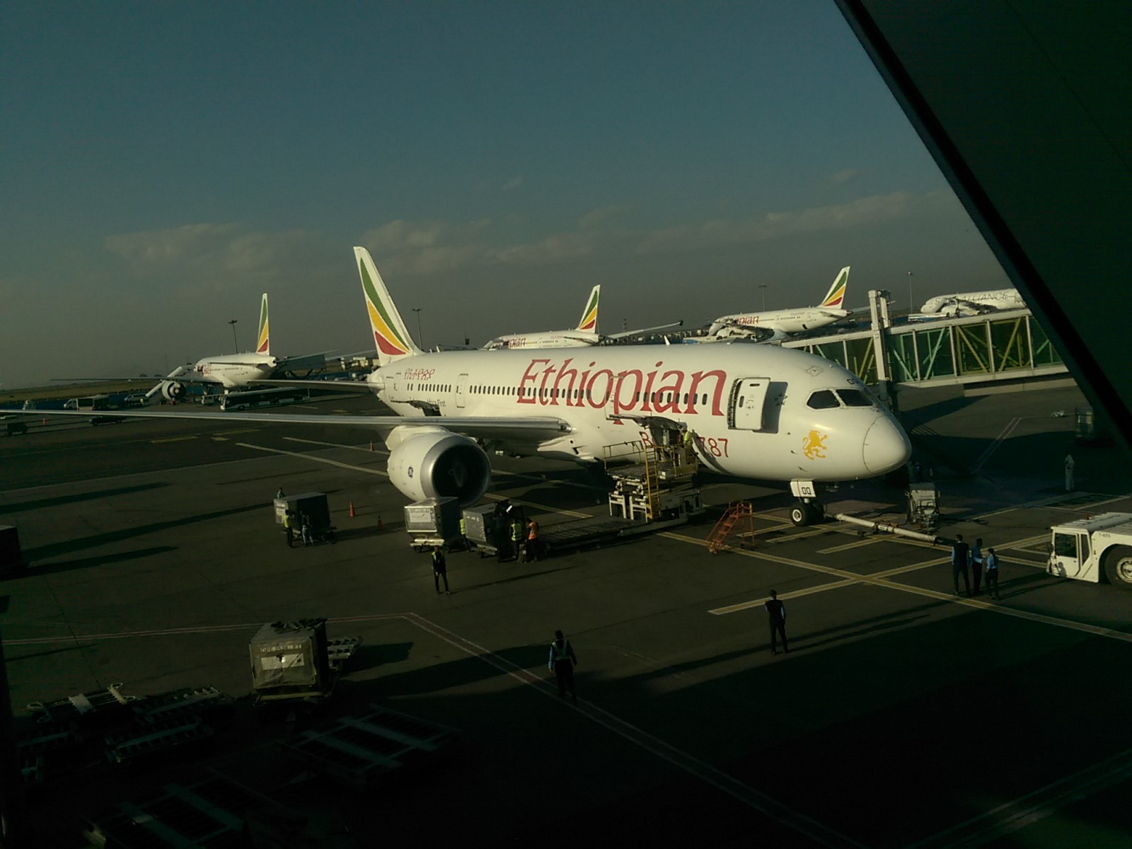 A white plane with Ethiopian written on the side in red letters on airport tarmac in front of a blue sky