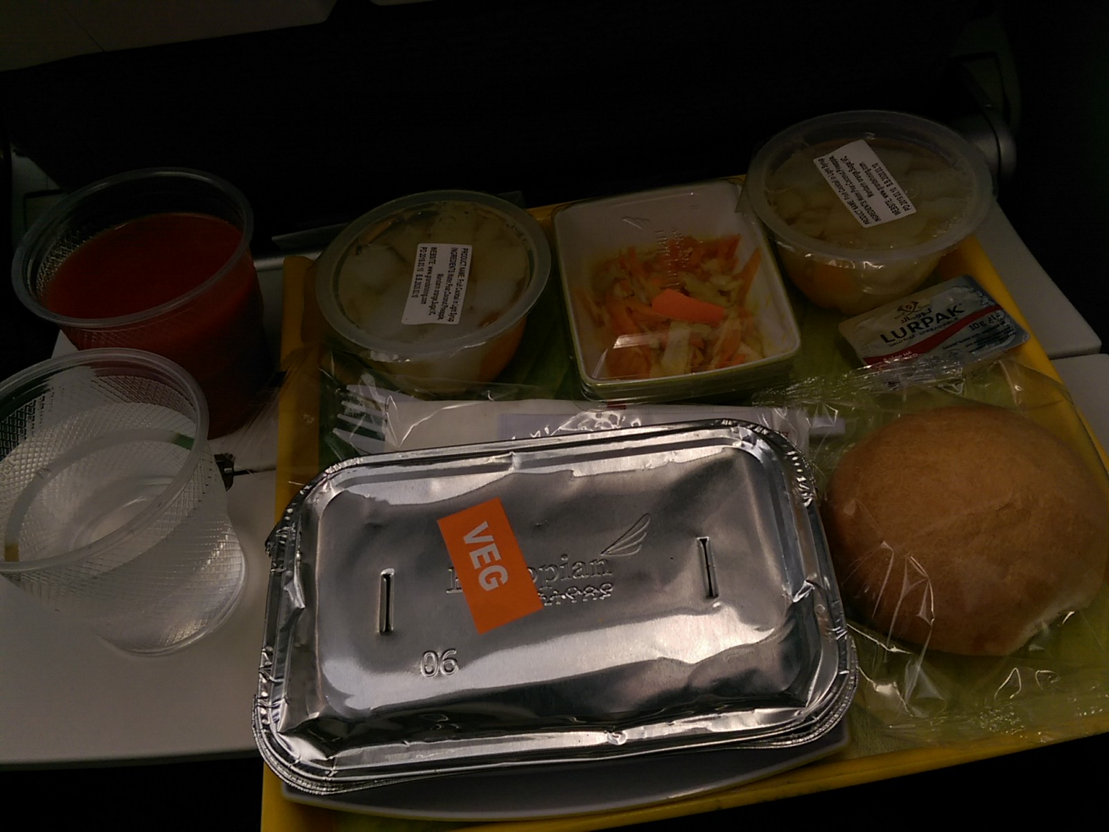 A seatback tray with plastic cups and foil covered boxes, fruit cups and a loaf of bread