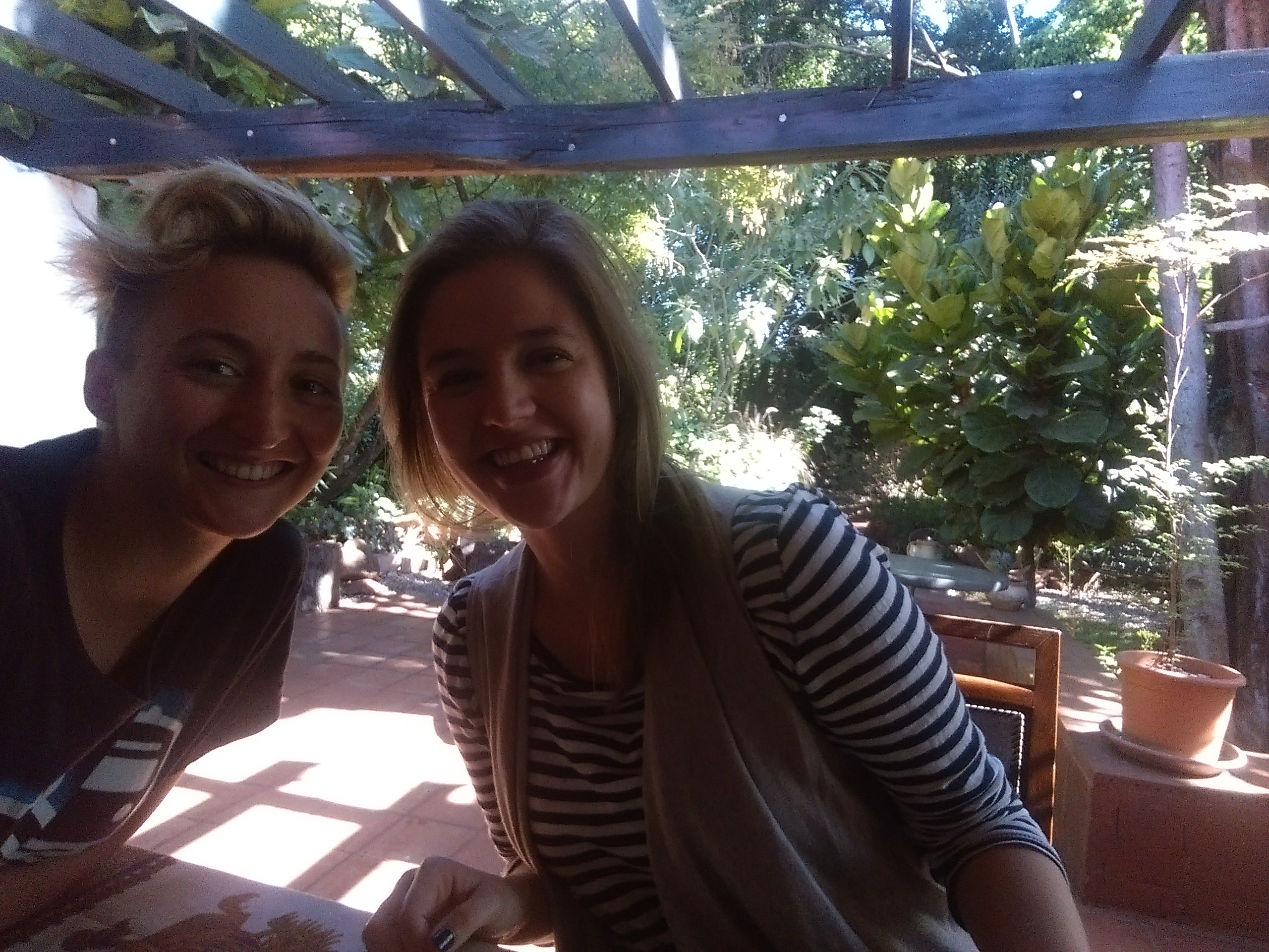 Two blondish ladies in black and white tshirts smiling at a table with a background of trees