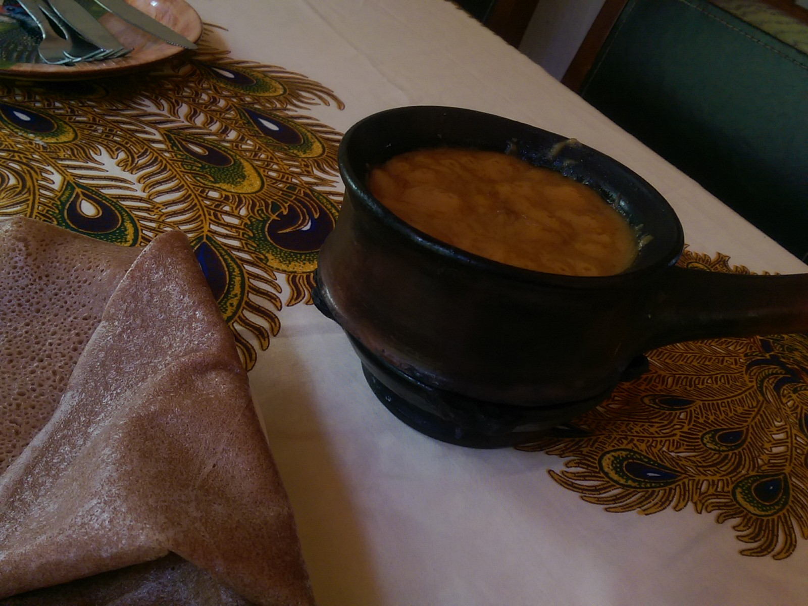 A plate of injera to the left and a metal pot with sizzling orange contents