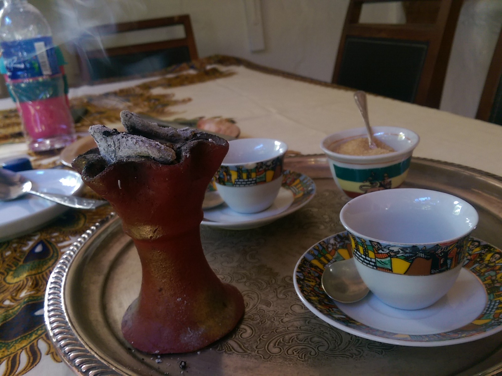A round metal tray with two white coffee cups and a funnel of smoldering incense