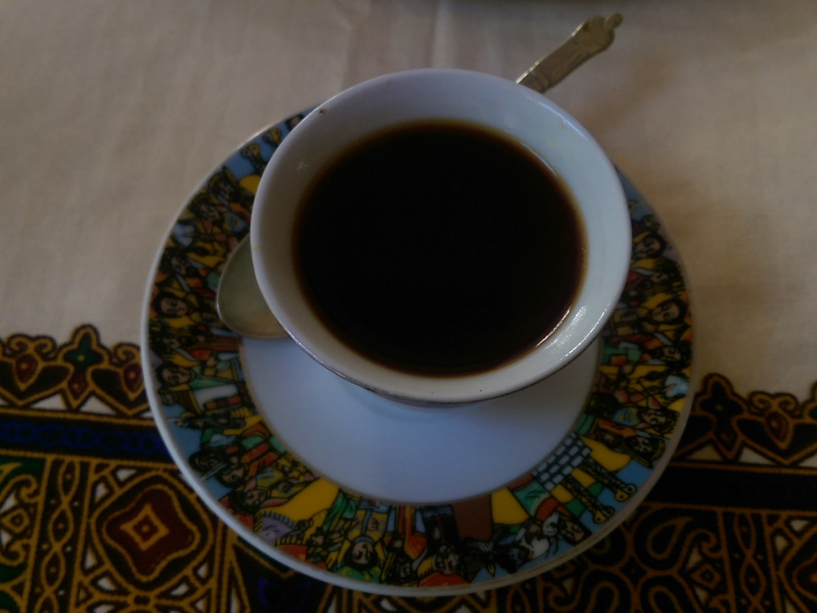 View from above of a small white coffeecup and saucer, filled with dark liquid
